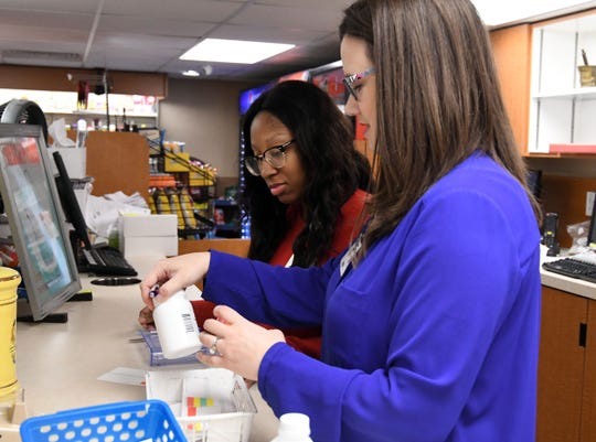 Laura Lofton, a pharmacist at Owl Drug Store at Hattiesburg Clinic, speaks with co-worker Keidran Beard.