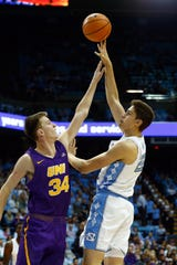Northern Iowa center Luke McDonnell (left) contests the shot of North Carolina's Walker Miller last season. McDonnell is second on the Panthers in scoring at 9.1 points per game heading into Saturday's meeting with Iowa at Wells Fargo Arena.