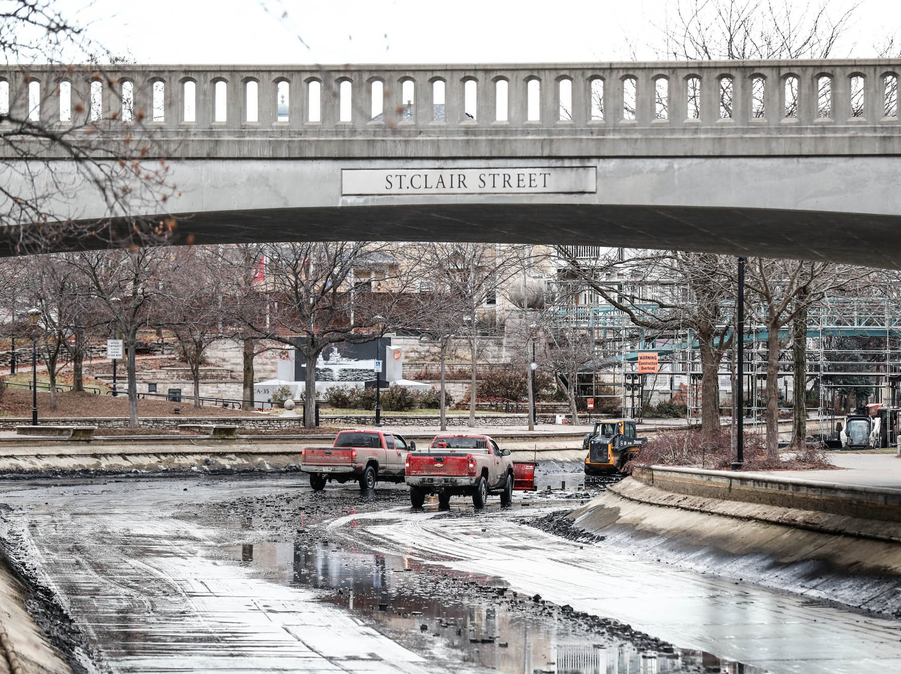 Crew members with Merrell Bros., Inc. use trucks and heavy machinery to remove sediment and organic growth from the Indiana Central Canal in downtown Indianapolis on Wednesday, Dec. 12, 2018. Here the crew works around the St. Claire St. Bridge.