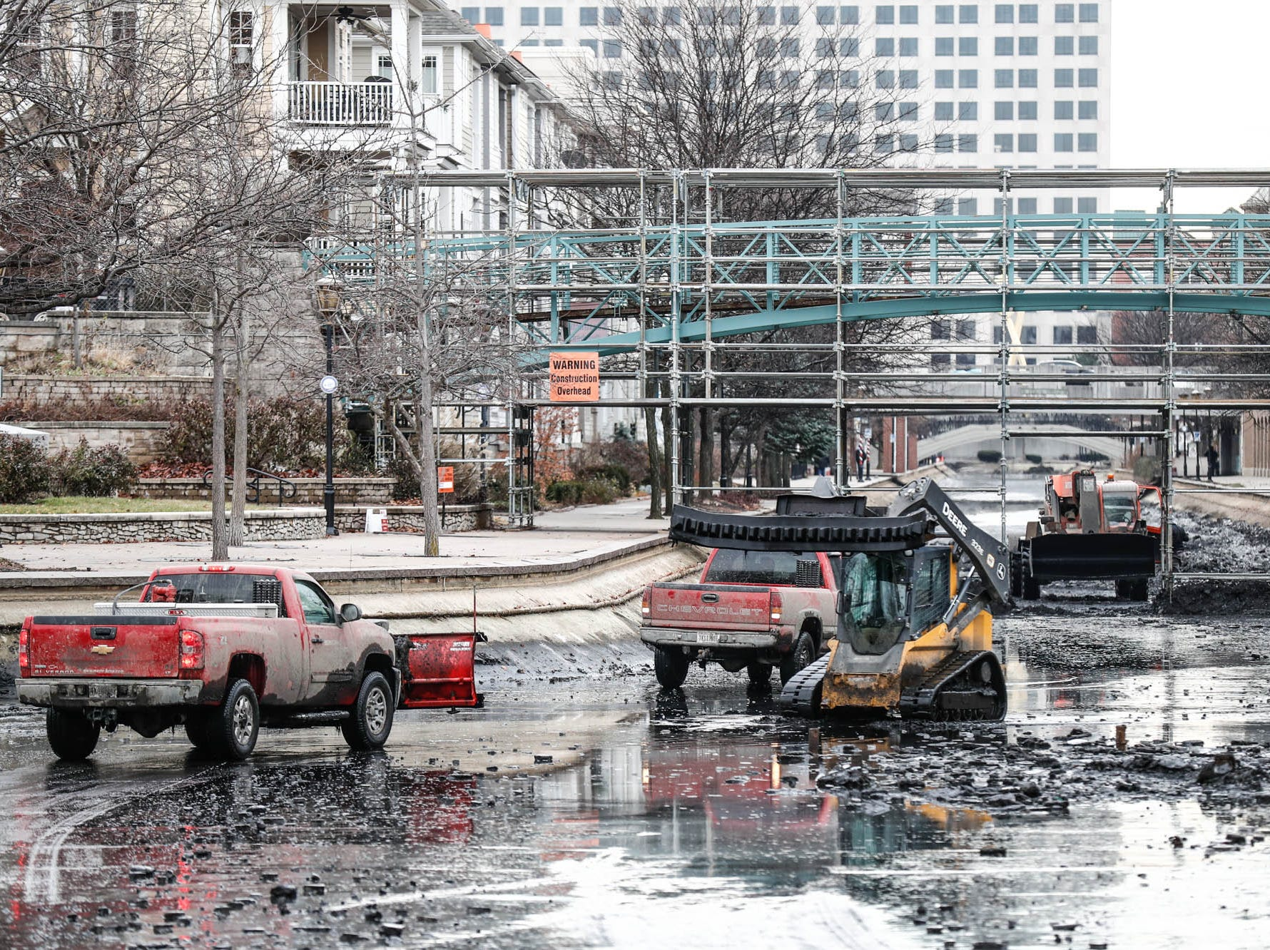 Crew members with Merrell Bros., Inc. use trucks and heavy machinery to remove sediment and organic growth from the Indiana Central Canal in downtown Indianapolis on Wednesday, Dec. 12, 2018.