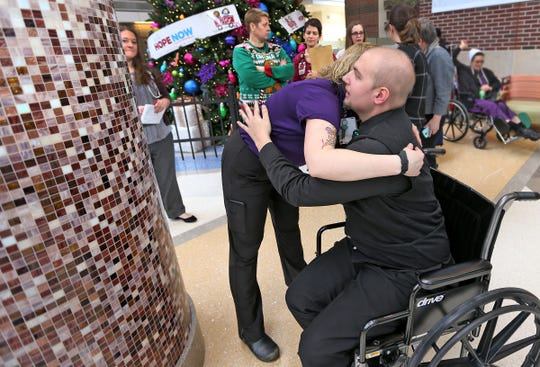 Indiana University Health Music Therapist Caitlin Krater, left, hugs Austin Hewitt, after he performed with the Eastern High School show choir at Riley Hospital, Friday, Dec. 14, 2018.  Hewitt recently lost his leg to bone cancer.  The show choir sang at the hospital as a way of giving back.  It meant a lot to Hewitt as some of the people who worked with him at Riley came to hear the choir perform.