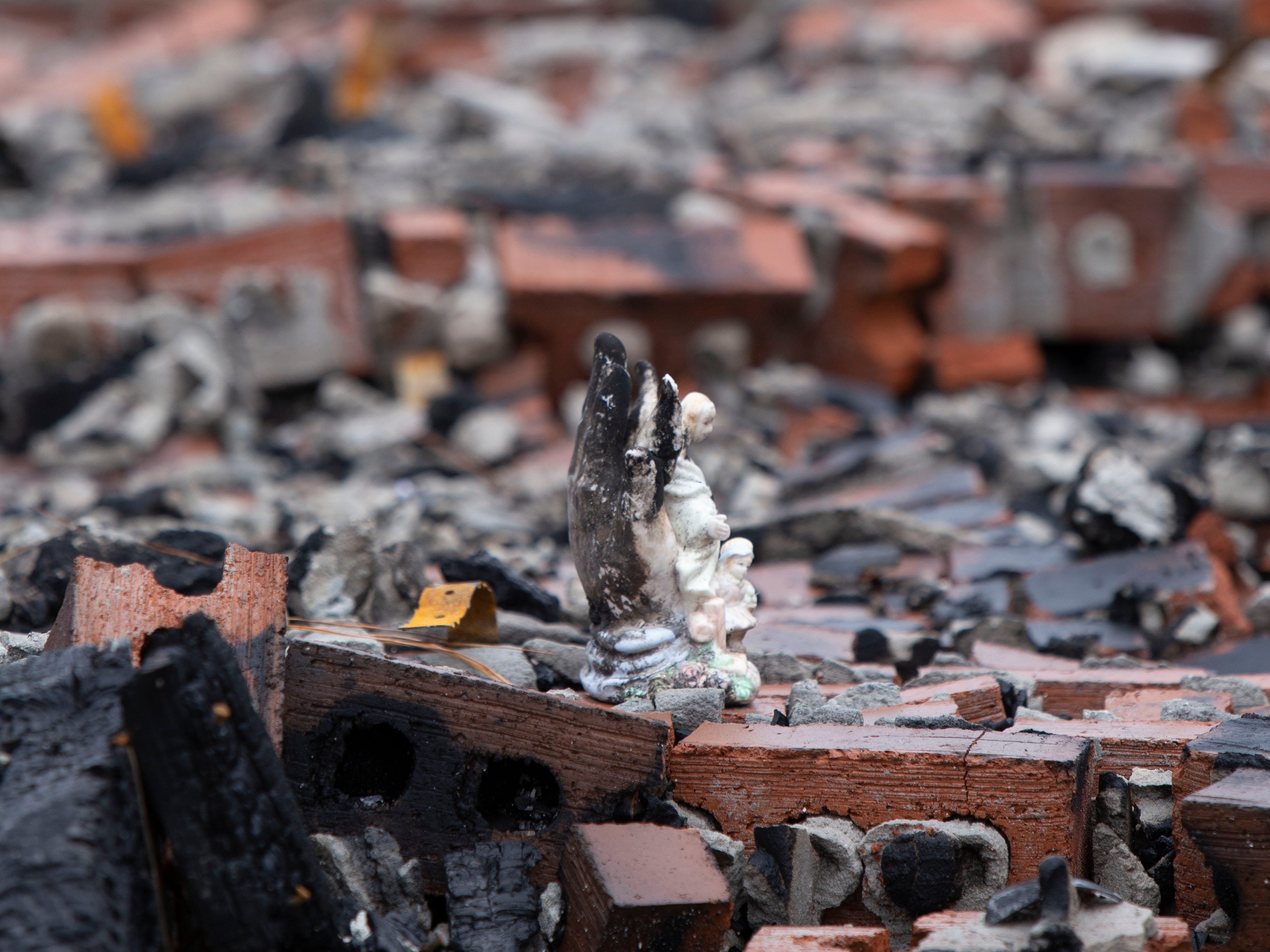 An angel figurine was one of the possessions left in the rubble of a house fire that destroyed the Haas home in Kiln, Mississippi, on Nov. 26, 2018. The angel's wings are burned with ash, but the children in front are unscathed.