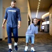 Dallas Cowboys quarterback Dak Prescott walks with 19-year-old artist Kendrell Daniels of Kemper County. Daniels traveled to Dallas as Dak's guest and presented him with a painting that Dak now keeps in the front area of his home. Daniels, who was born with no arms but has learned to paint with his feet, inspires  Prescott.