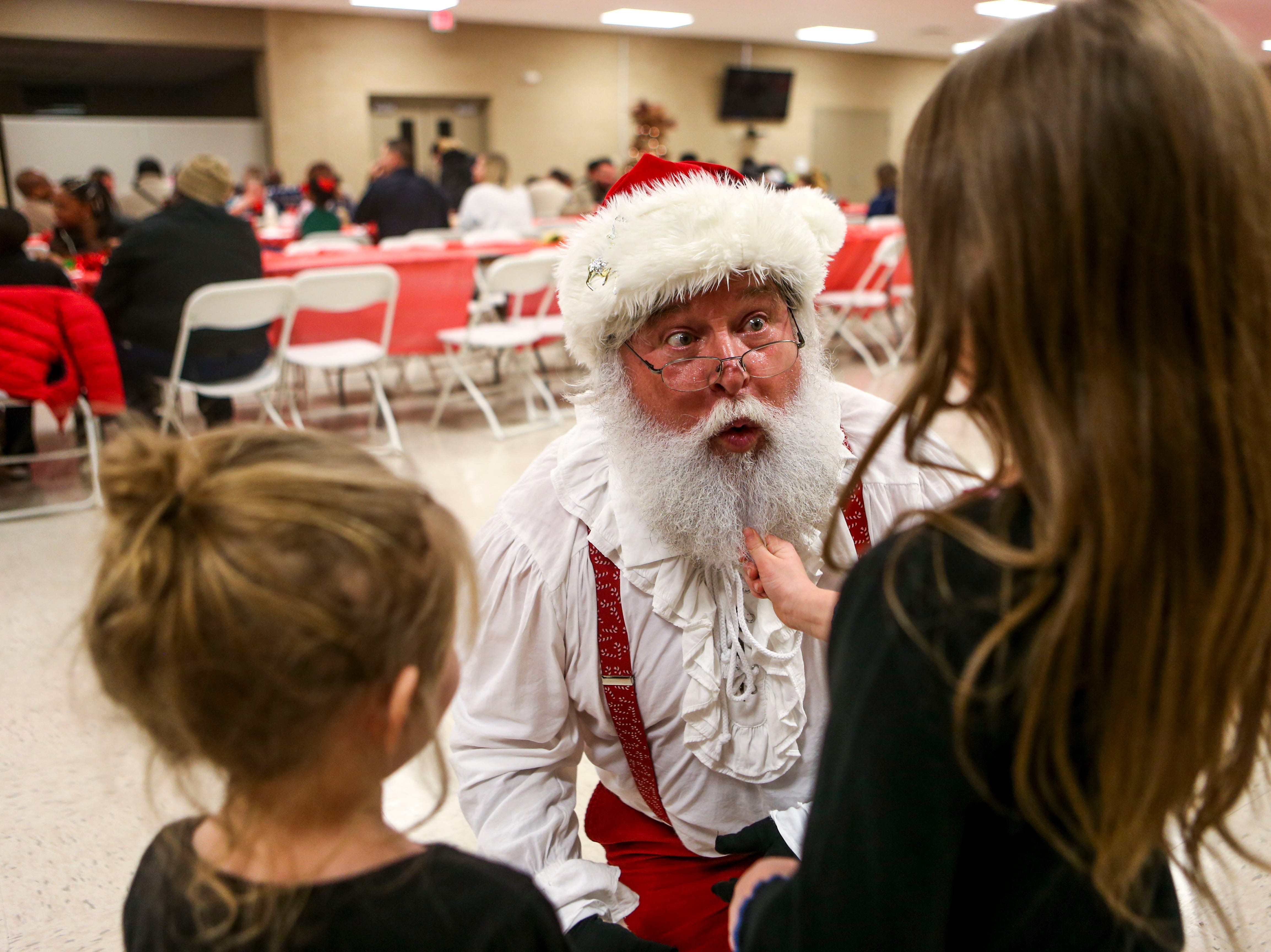 Two participants pull down on Santa Claus' beard during the matching time for Shop with a Cop at Hawkins-Whitby Fema Community Safe Room in Milan, Tenn., on Thursday, Dec. 13, 2018.