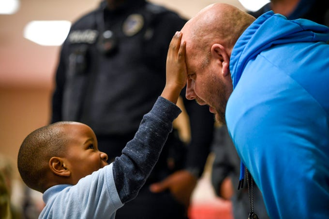 Bobby Cliff III, 4, reaches up and touches the head of Detective Chris Vandiver, who took Bobby shopping the previous year as well during the matching time for Shop with a Cop at Hawkins-Whitby Fema Community Safe Room in Milan, Tenn., on Thursday, Dec. 13, 2018. In the previous year, Bobby's father had shot his mother multiple times after an argument, but Vandiver noted that Bobby seemed to be in high spirits both years despite the traumatic experience.