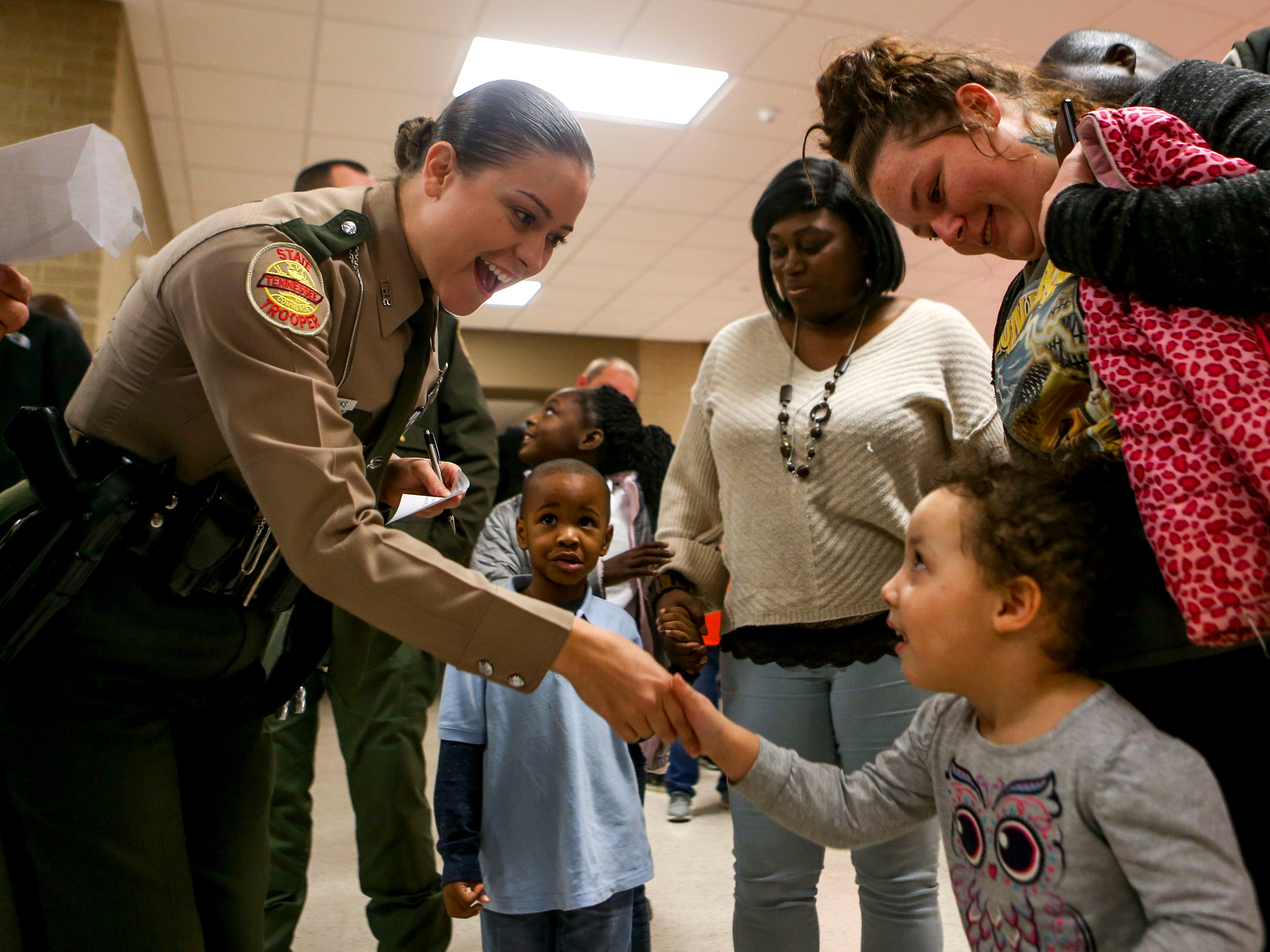 Trooper Jena Eubanks reaches down to shake hands with her match, Heavenly Gladney, 3, during the matching time for Shop with a Cop at Hawkins-Whitby Fema Community Safe Room in Milan, Tenn., on Thursday, Dec. 13, 2018.