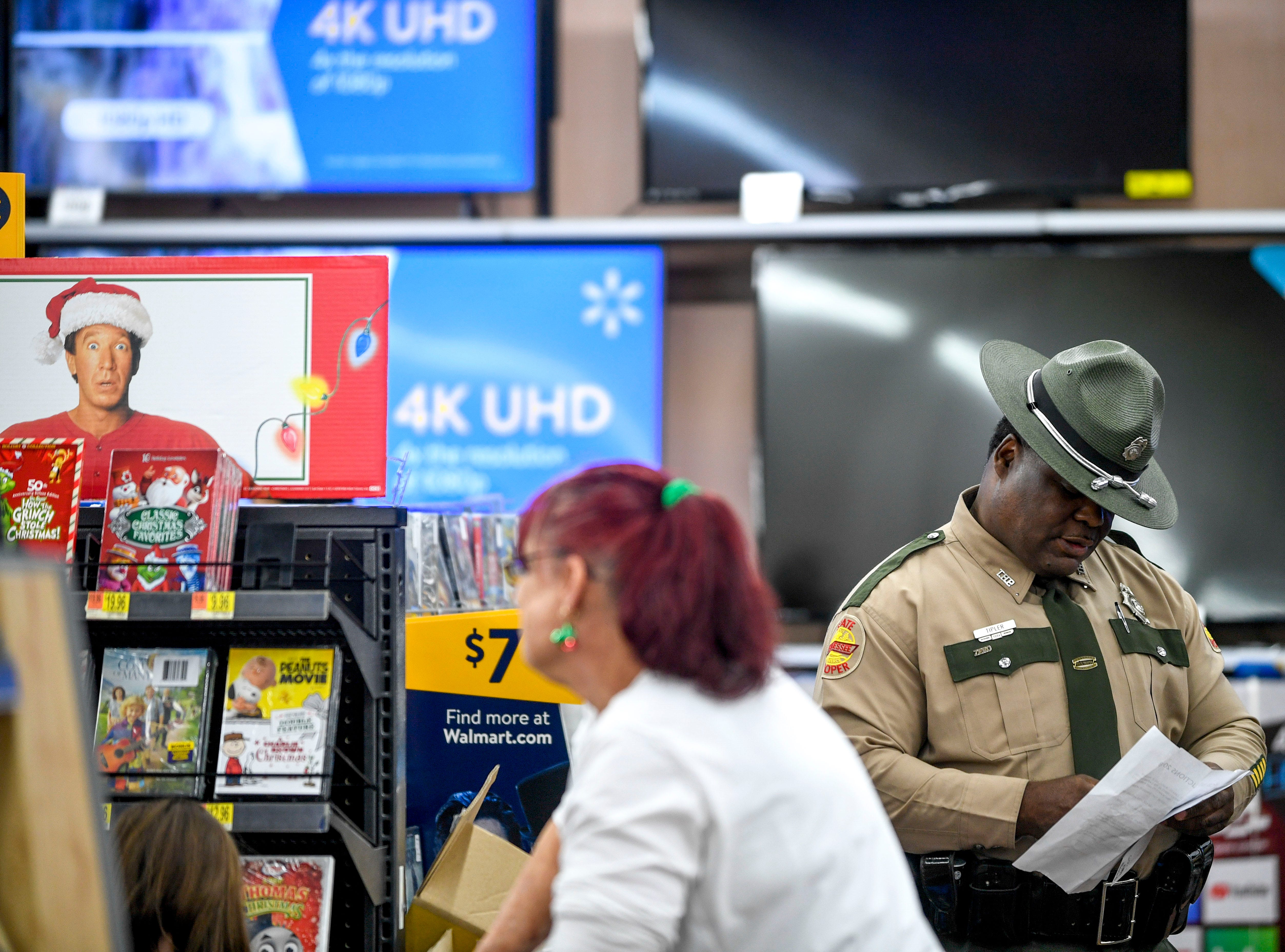 Trooper Jerry Tipler takes notes on his cell phone while his partners select DVD's during shopping time for the annual Shop with a Cop program at Walmart in Milan, Tenn., on Thursday, Dec. 13, 2018.