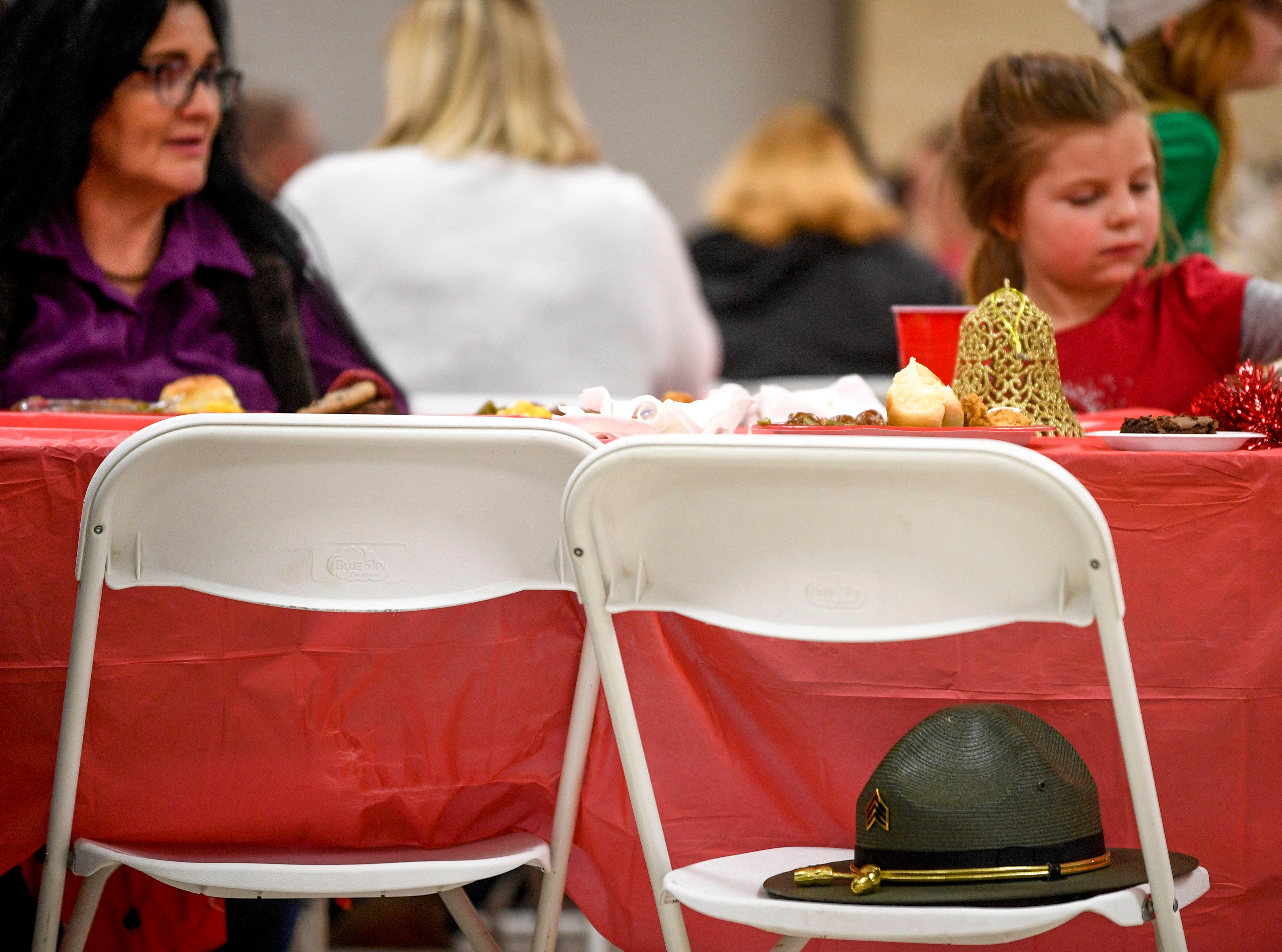 A state trooper leaves their hat to mark their seat near their kids during the matching time for Shop with a Cop at Hawkins-Whitby Fema Community Safe Room in Milan, Tenn., on Thursday, Dec. 13, 2018.