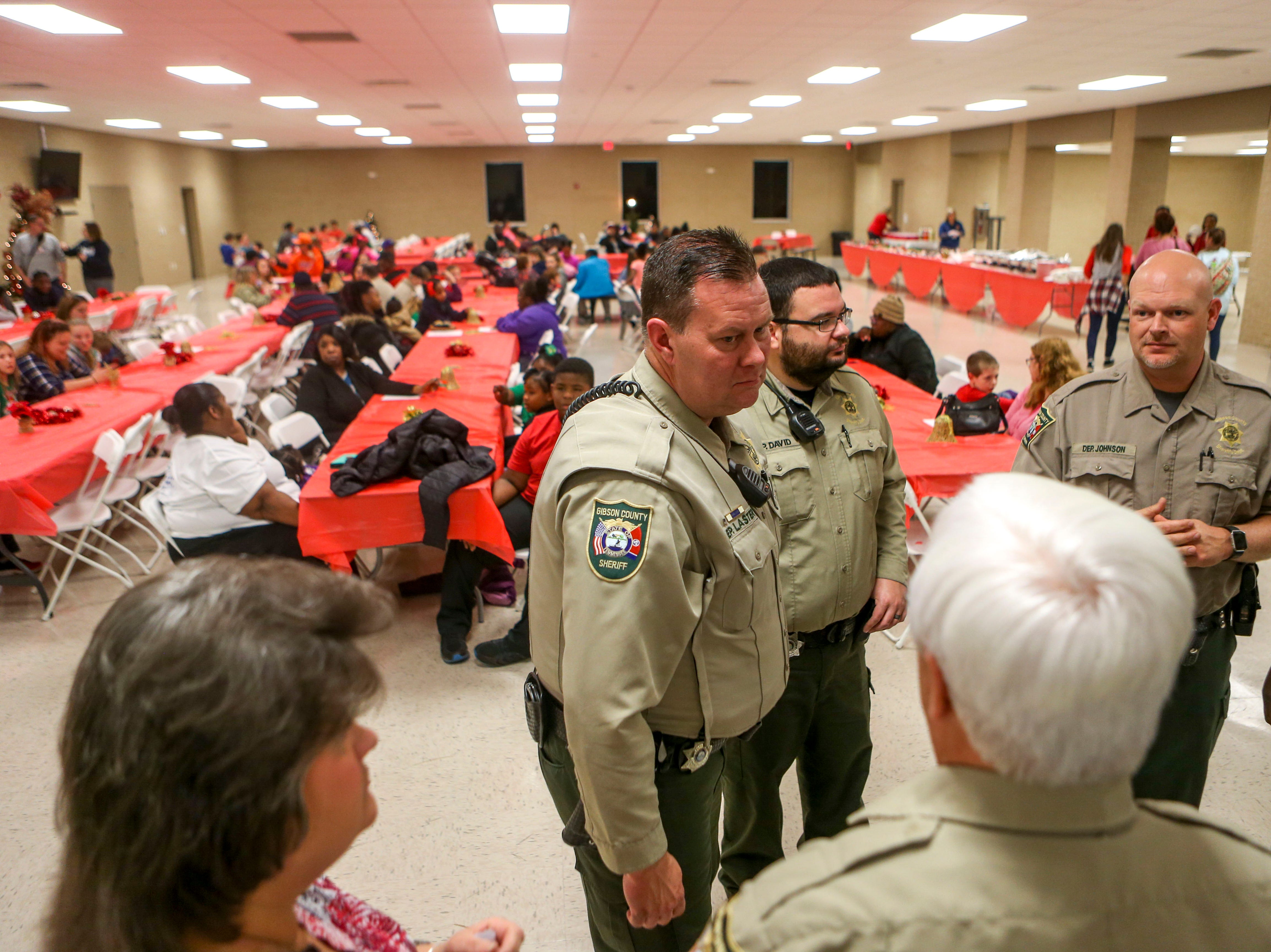Law enforcement officers speak amongst themselves before starting the matching announcements during the matching time for Shop with a Cop at Hawkins-Whitby Fema Community Safe Room in Milan, Tenn., on Thursday, Dec. 13, 2018.