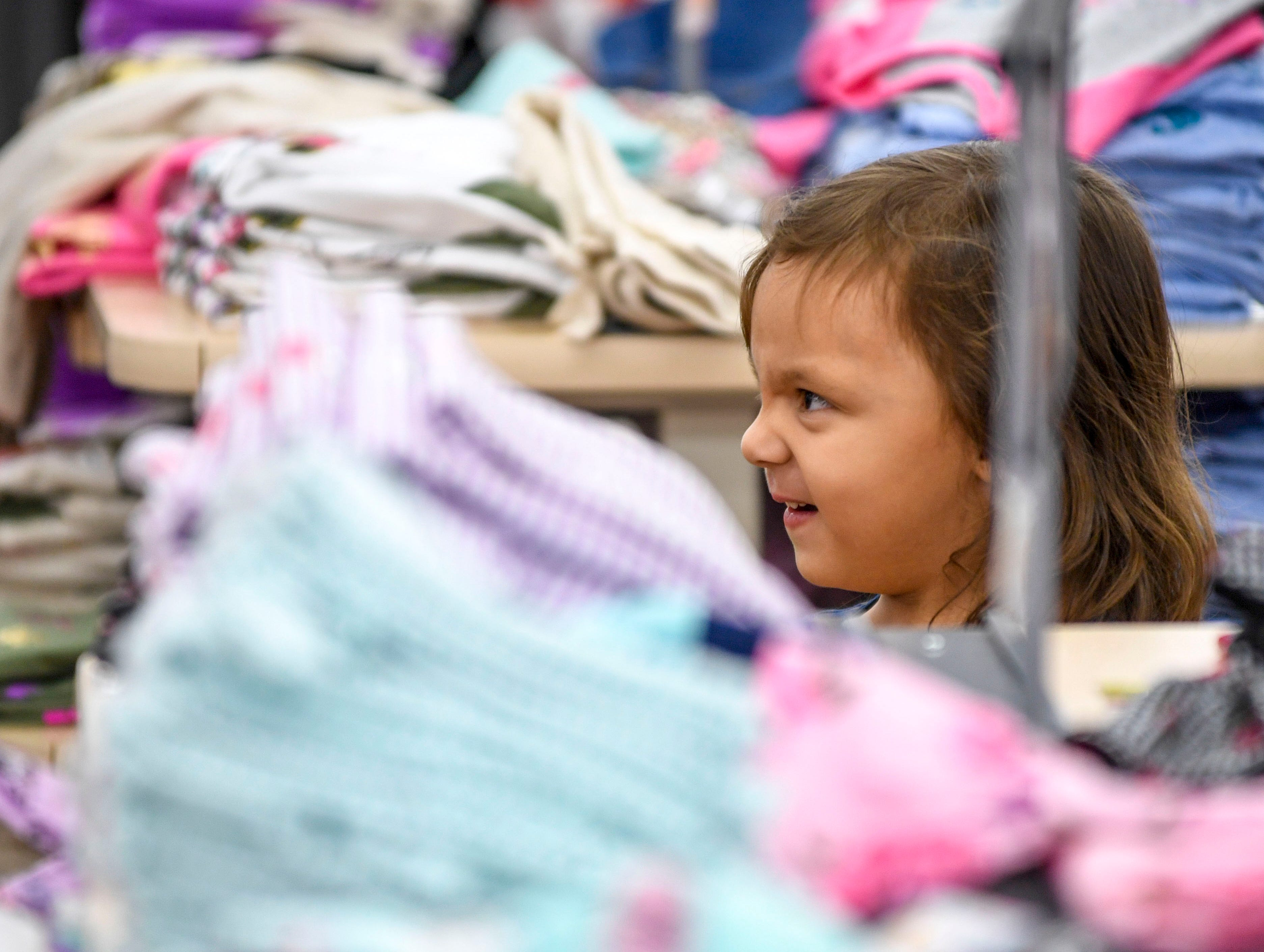 Allie Gordon, 3, reacts while shopping for clothes during shopping time for the annual Shop with a Cop program at Walmart in Milan, Tenn., on Thursday, Dec. 13, 2018.
