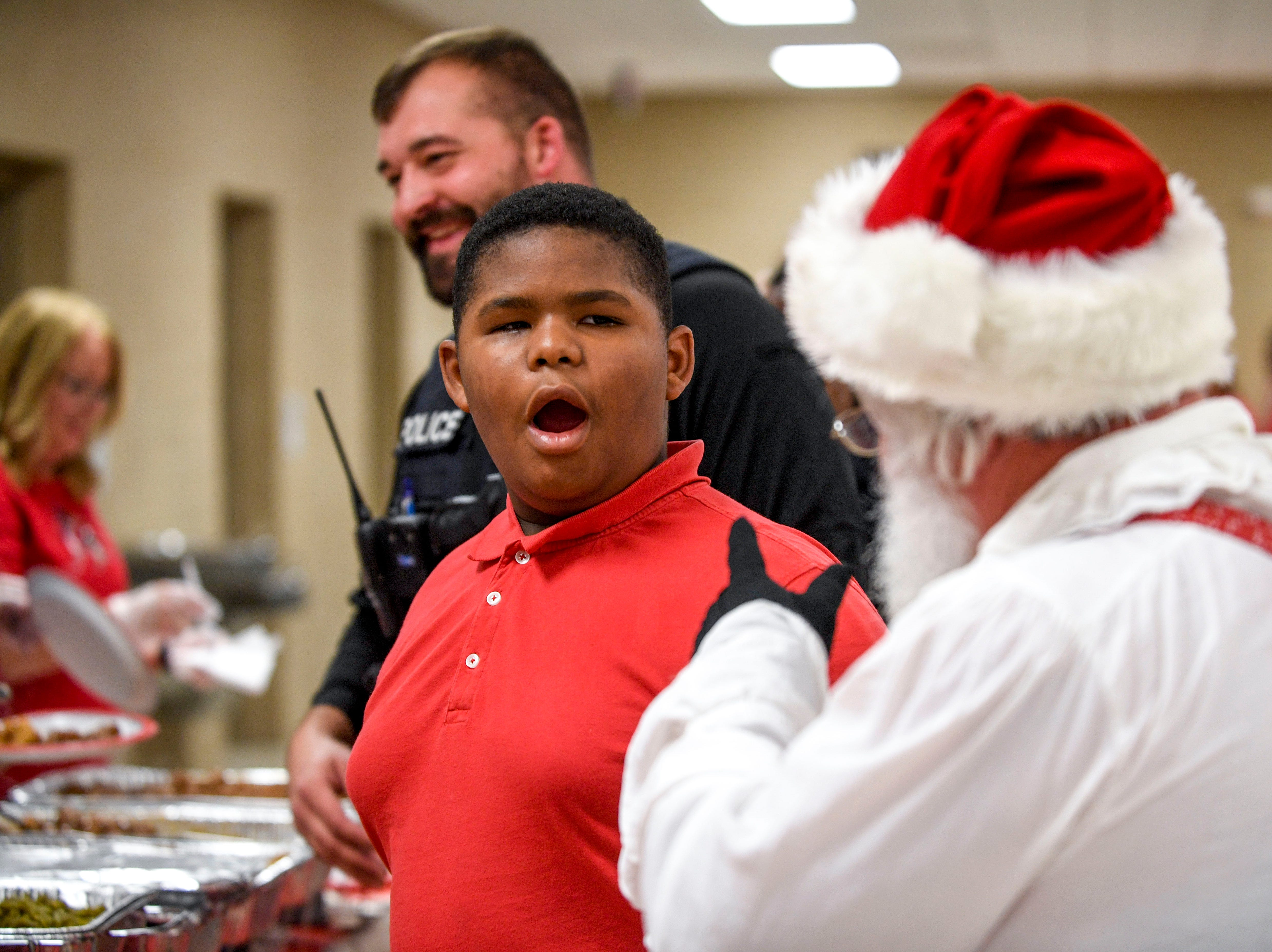 Santa Claus points out that Omar Pirtle's, 11, eyes indicate that he backtalks a lot, to which Pirtle reacts during the matching time for Shop with a Cop at Hawkins-Whitby Fema Community Safe Room in Milan, Tenn., on Thursday, Dec. 13, 2018.