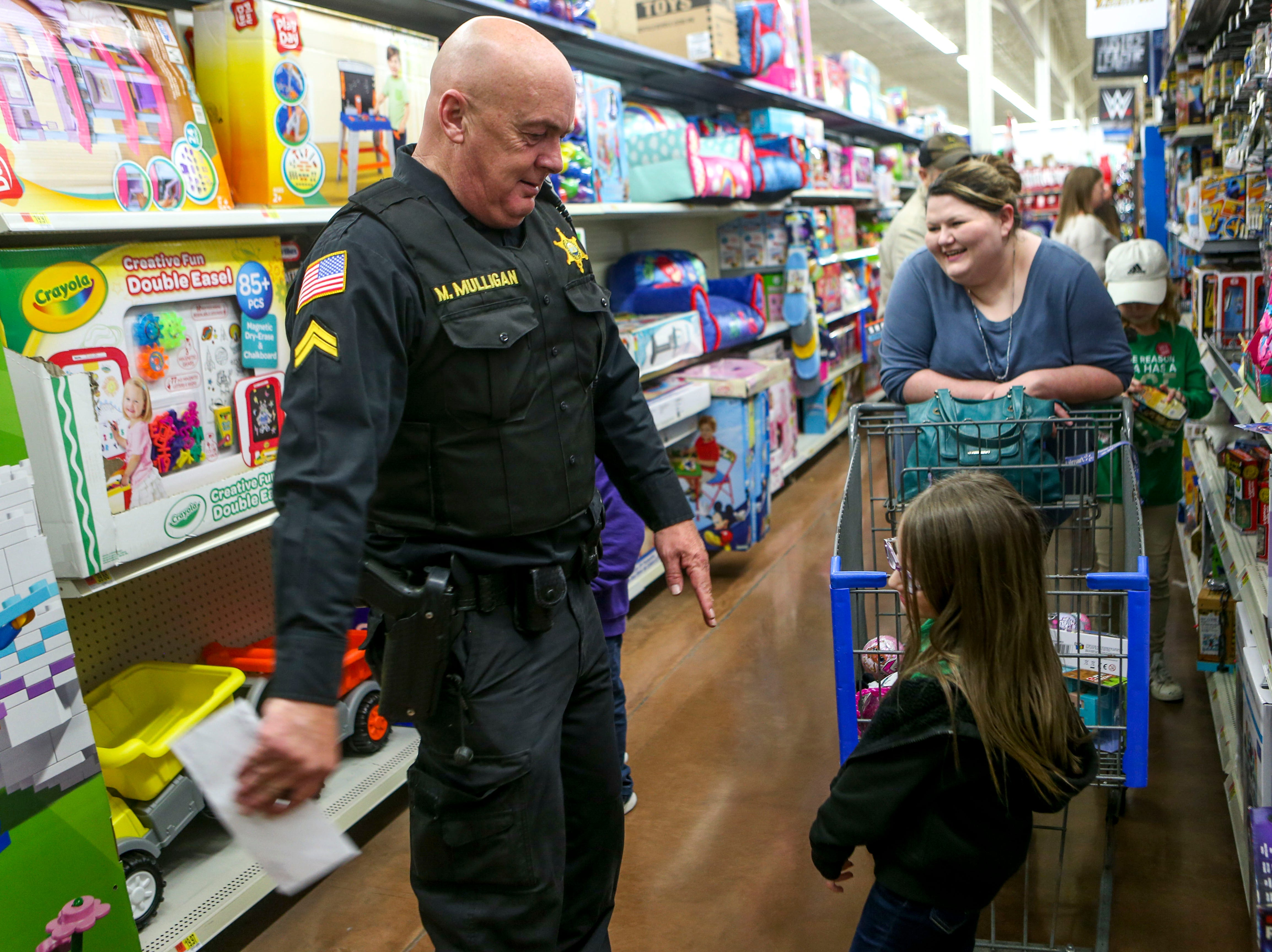 Carroll County Sheriff deputy Mike Mulligan does the floss dance with Layci Moore, 6, during shopping time for the annual Shop with a Cop program at Walmart in Milan, Tenn., on Thursday, Dec. 13, 2018.
