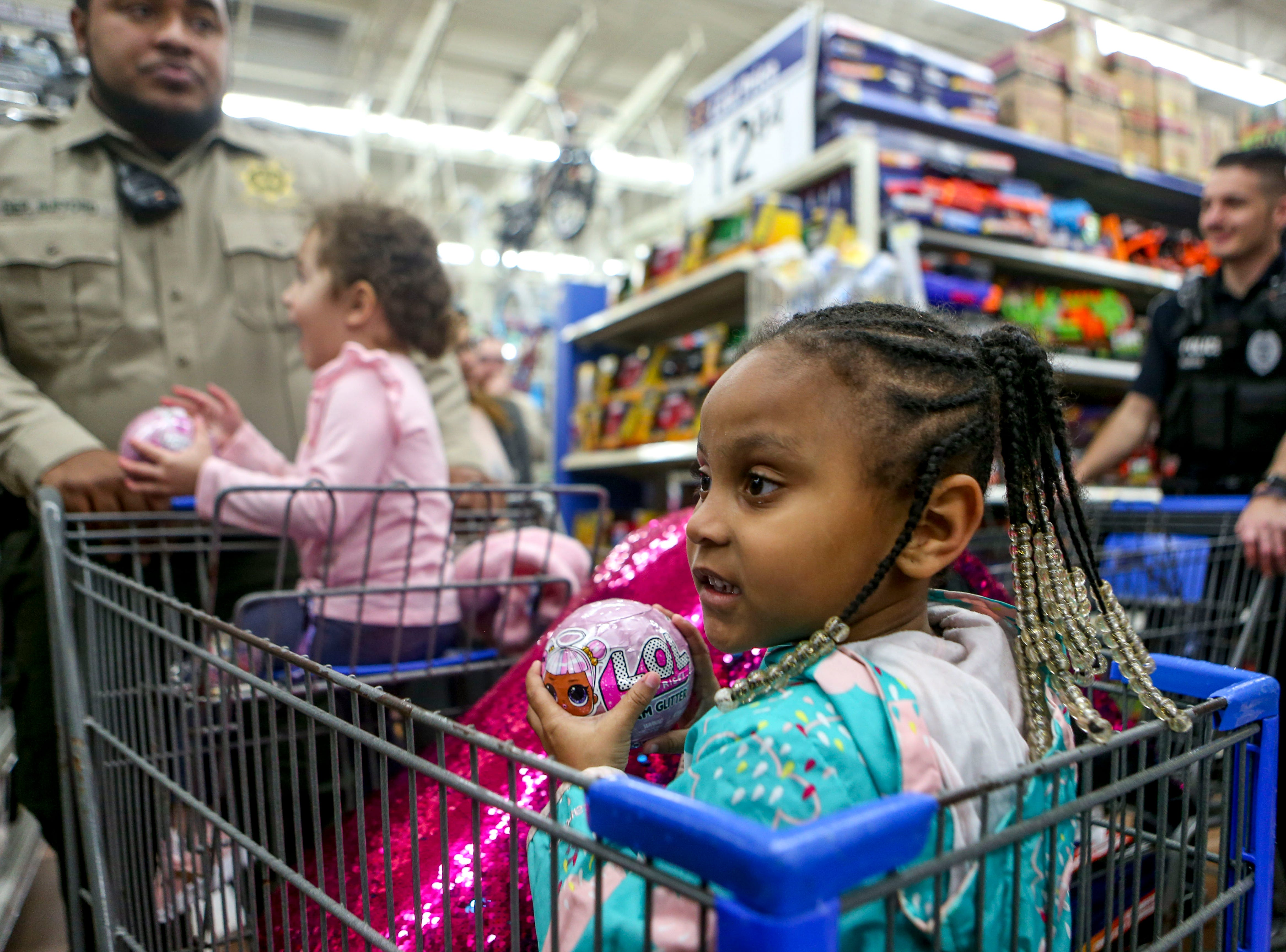 A young shopper gazes down the aisles of toys to snag during shopping time for the annual Shop with a Cop program at Walmart in Milan, Tenn., on Thursday, Dec. 13, 2018.