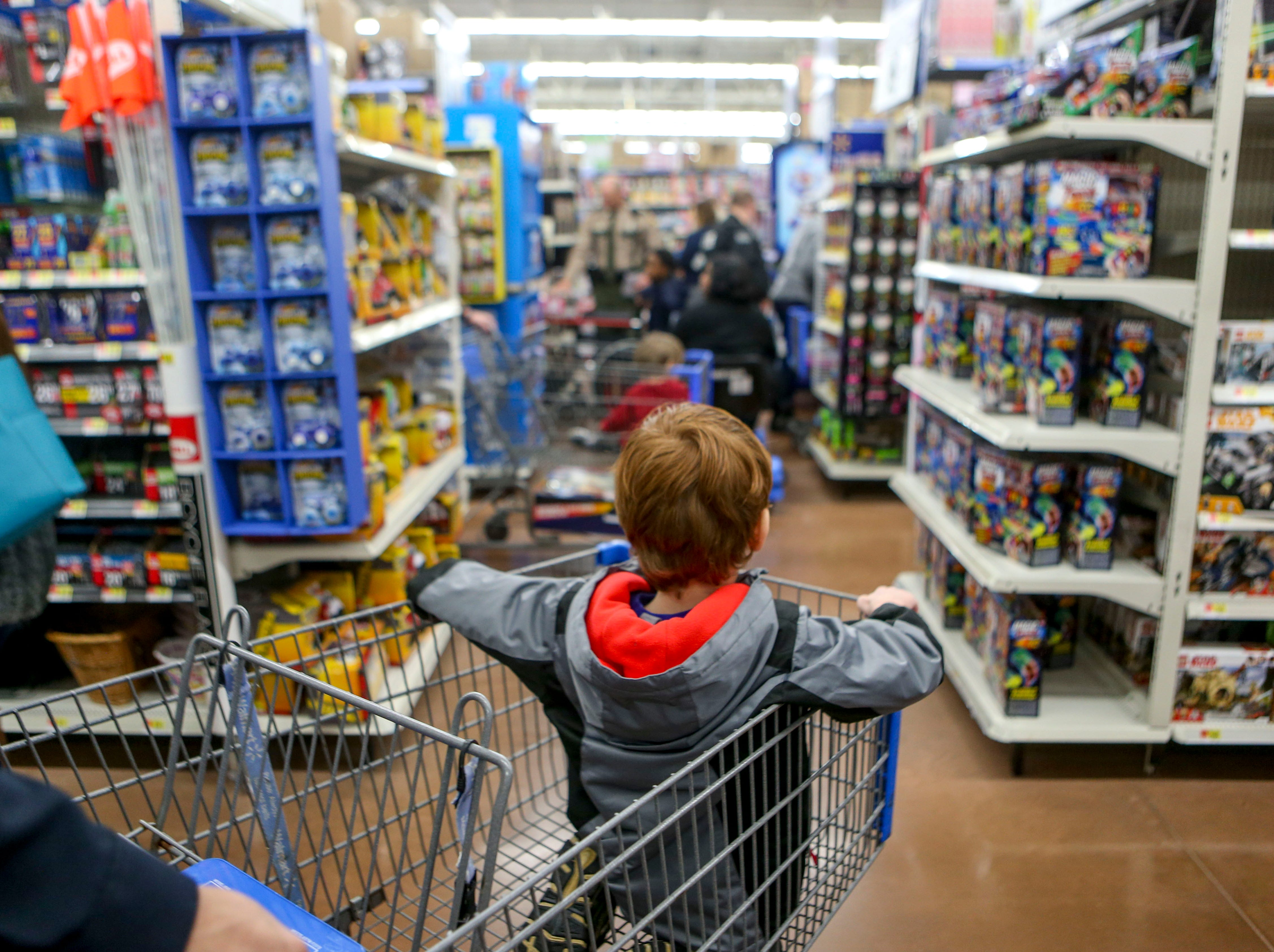 A boy looks out over the vast expanse of toys in front of him, with an empty cart and a balance to spend during shopping time for the annual Shop with a Cop program at Walmart in Milan, Tenn., on Thursday, Dec. 13, 2018.