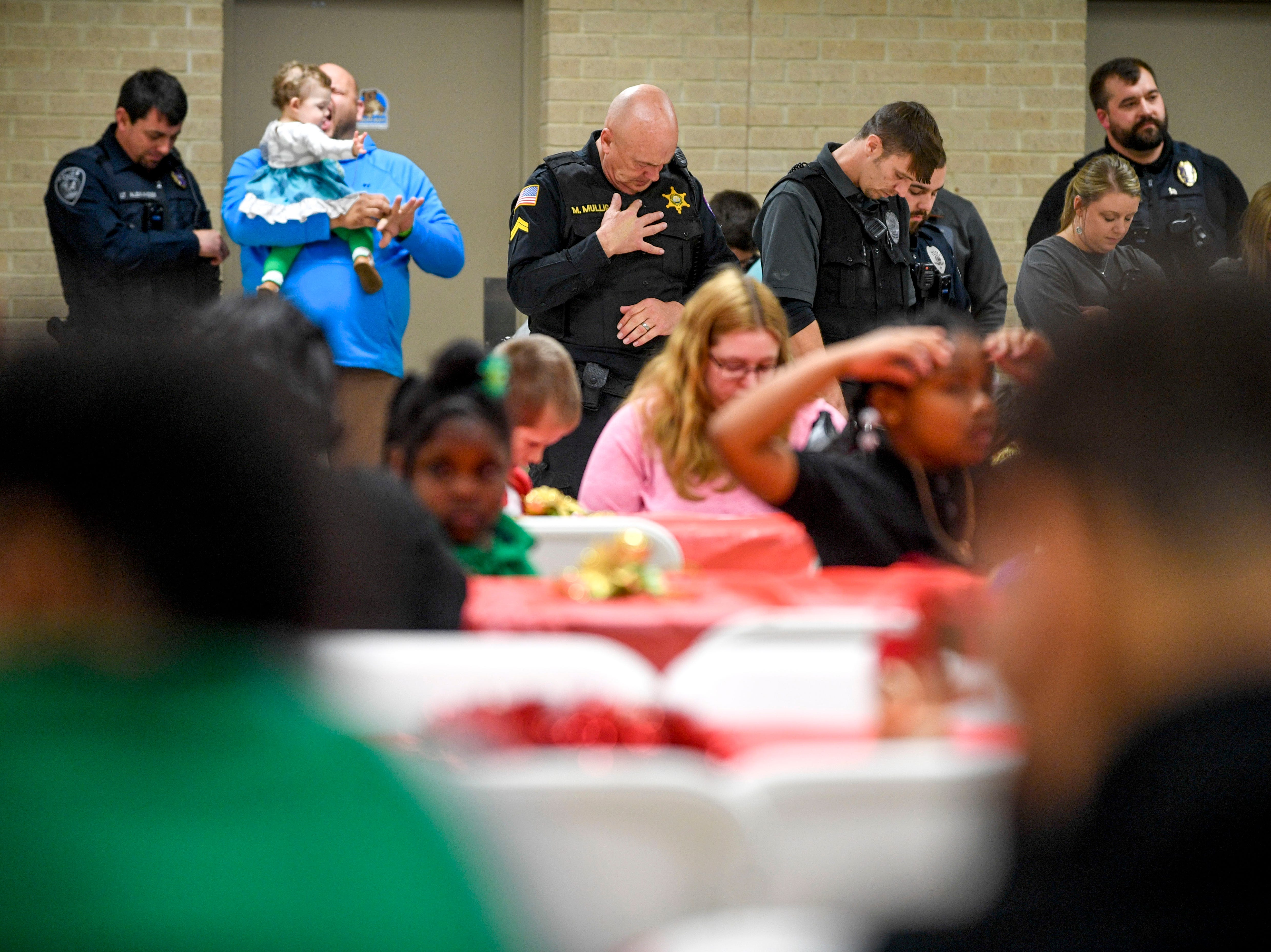 Law enforcement officers bow their heads for a prayer during the matching time for Shop with a Cop at Hawkins-Whitby Fema Community Safe Room in Milan, Tenn., on Thursday, Dec. 13, 2018.
