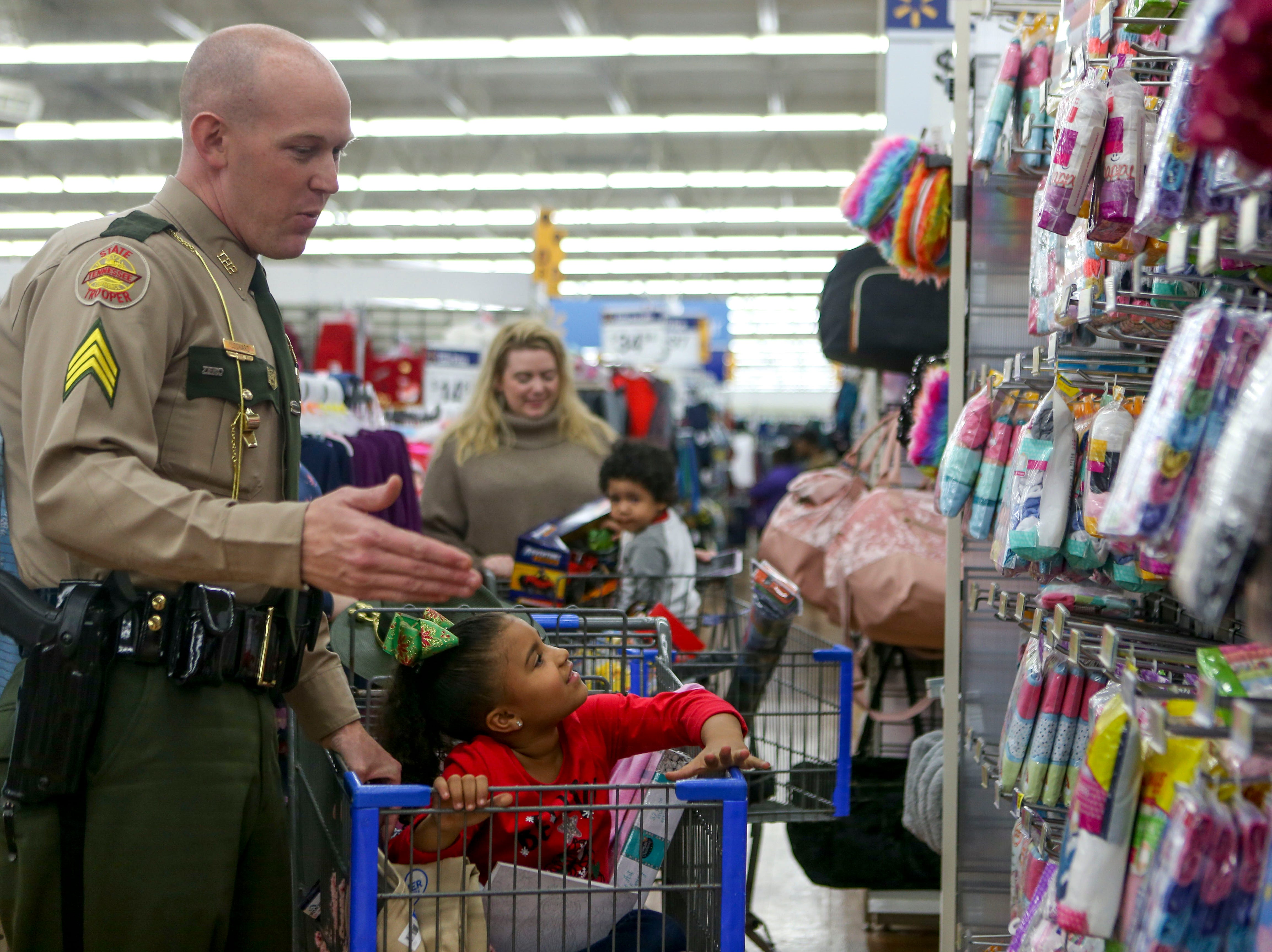 Trooper Michael Lockard helps his partner Kastle Mays, 5, examine clothing to purchase during the shopping time for the annual Shop with a Cop program at Walmart in Milan, Tenn., on Thursday, Dec. 13, 2018.