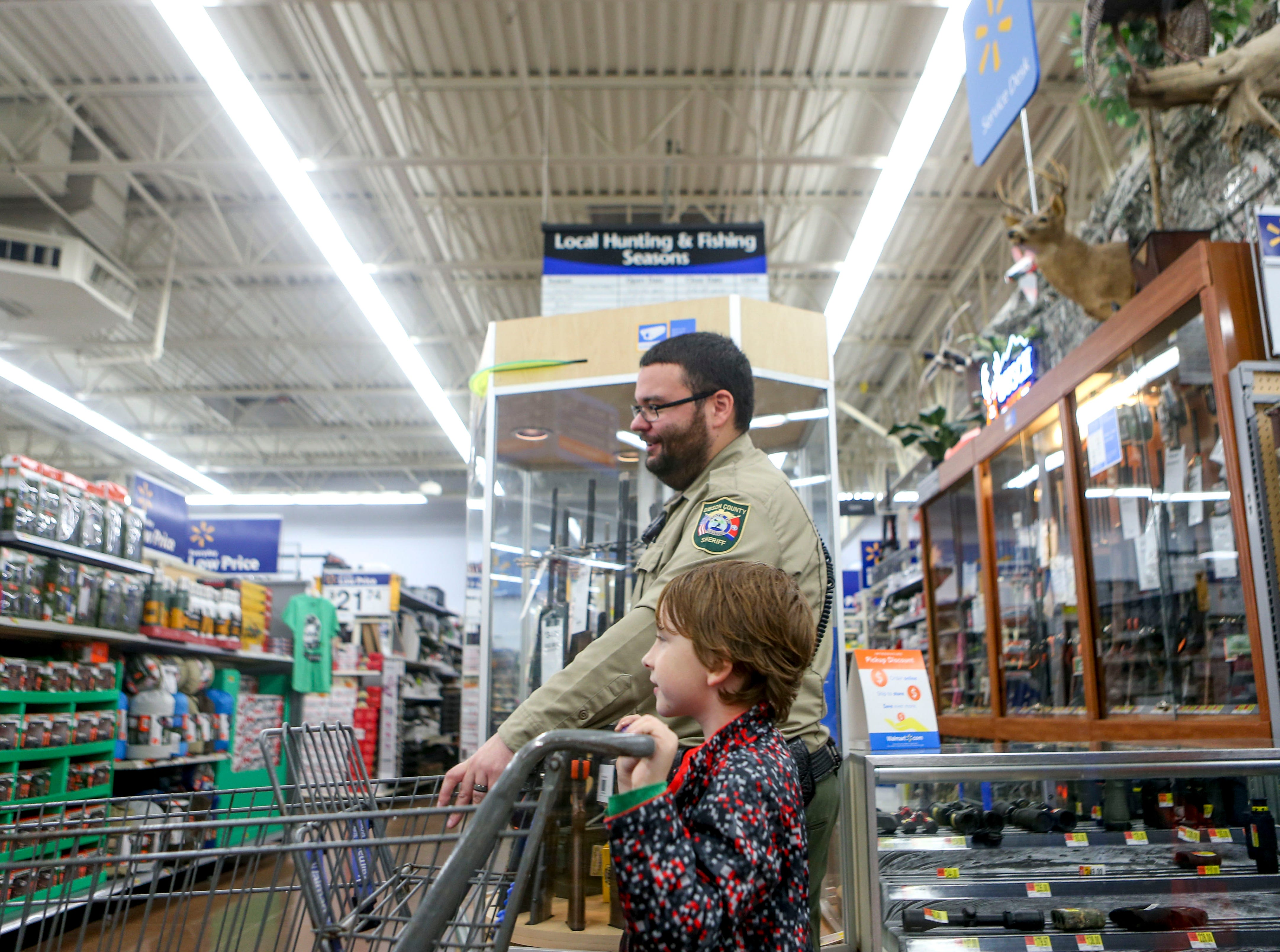 A Sheriff's deputy and his partner walk through the aisles shopping for various items during shopping time for the annual Shop with a Cop program at Walmart in Milan, Tenn., on Thursday, Dec. 13, 2018.