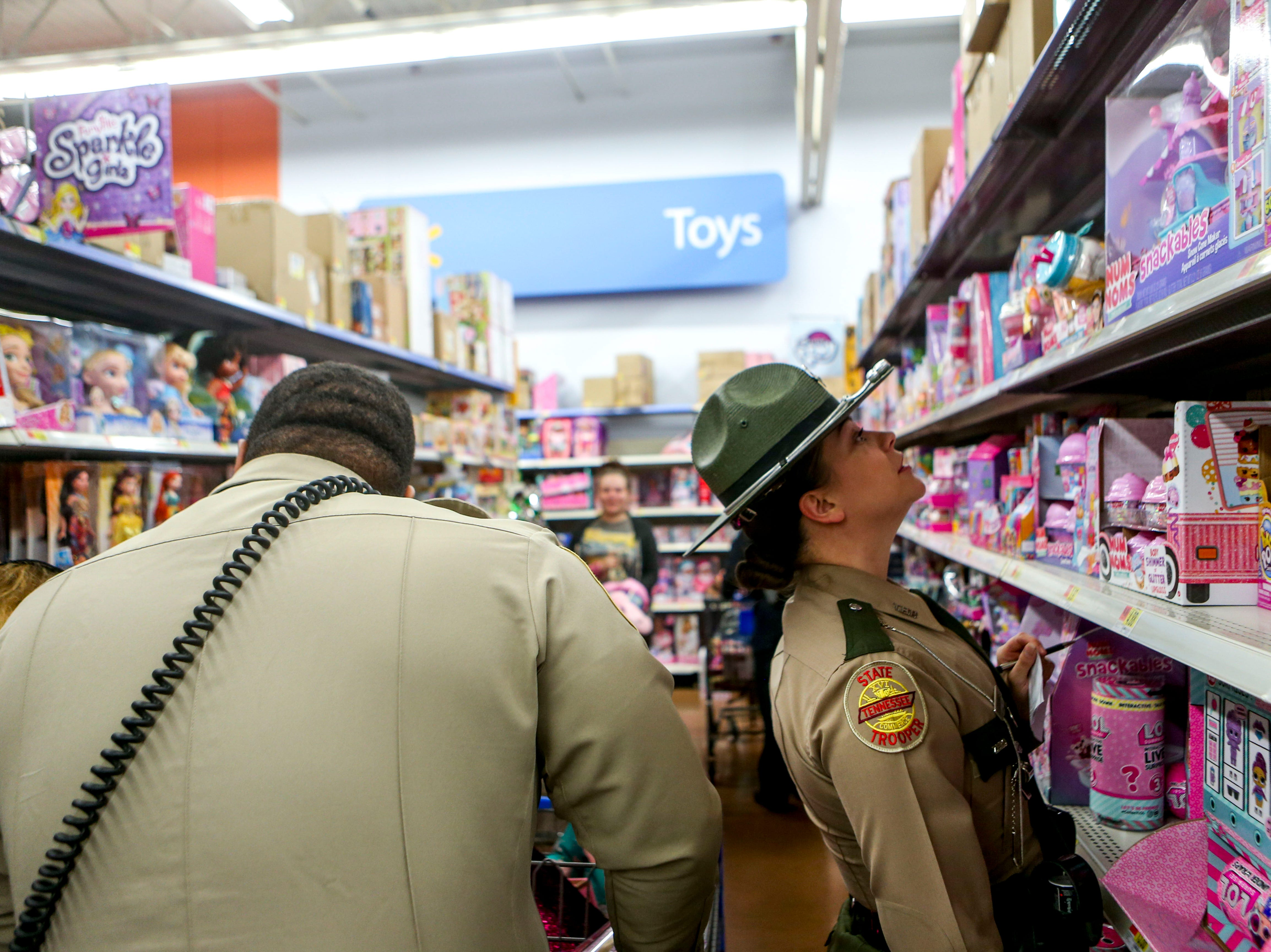 Trooper Eubanks stares up the walls of toys during shopping time for the annual Shop with a Cop program at Walmart in Milan, Tenn., on Thursday, Dec. 13, 2018.