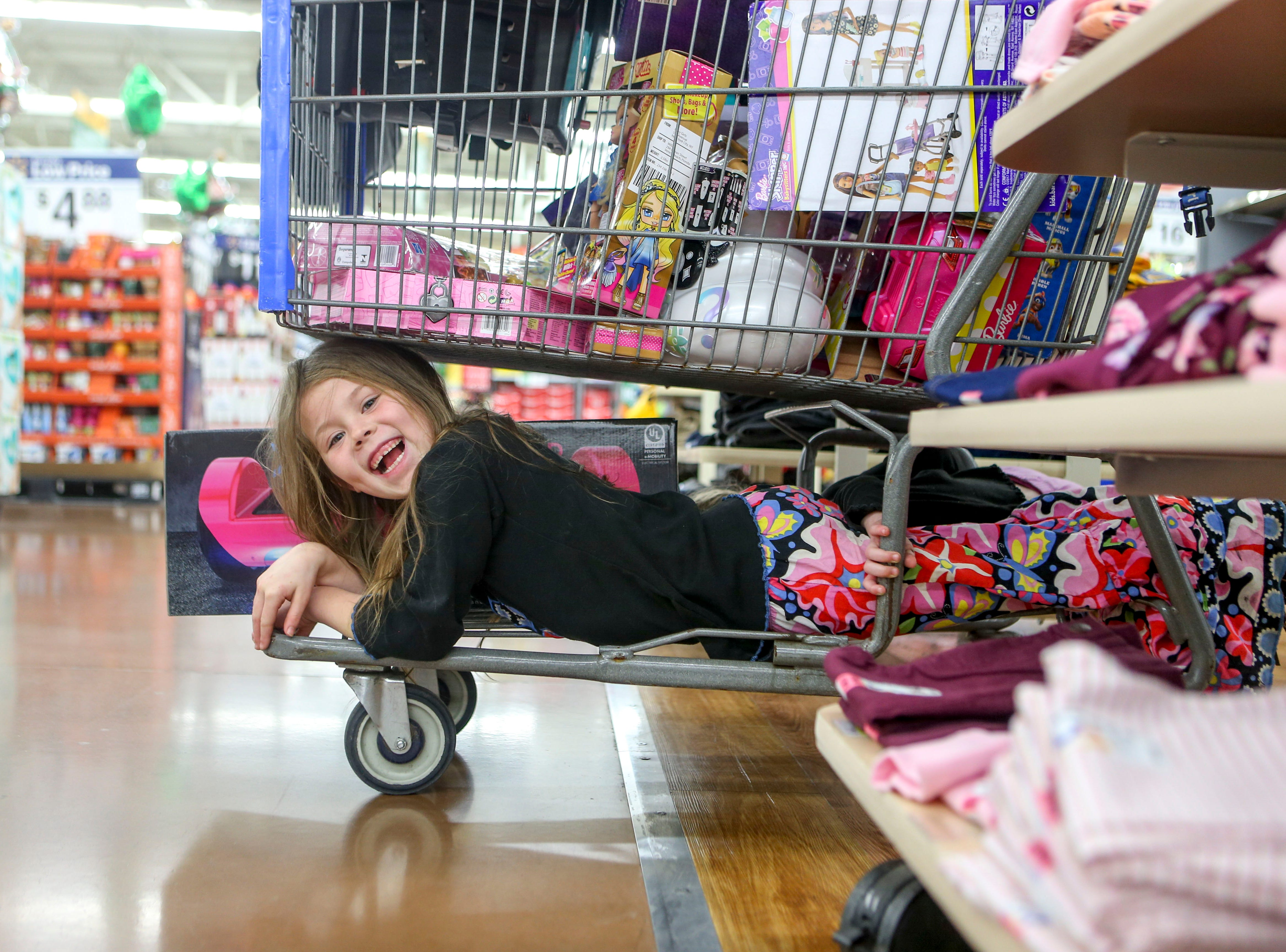 Bailey Sutcliffe, 4, exclaims while being pushed around in the bottom of a shopping cart during shopping time for the annual Shop with a Cop program at Walmart in Milan, Tenn., on Thursday, Dec. 13, 2018.