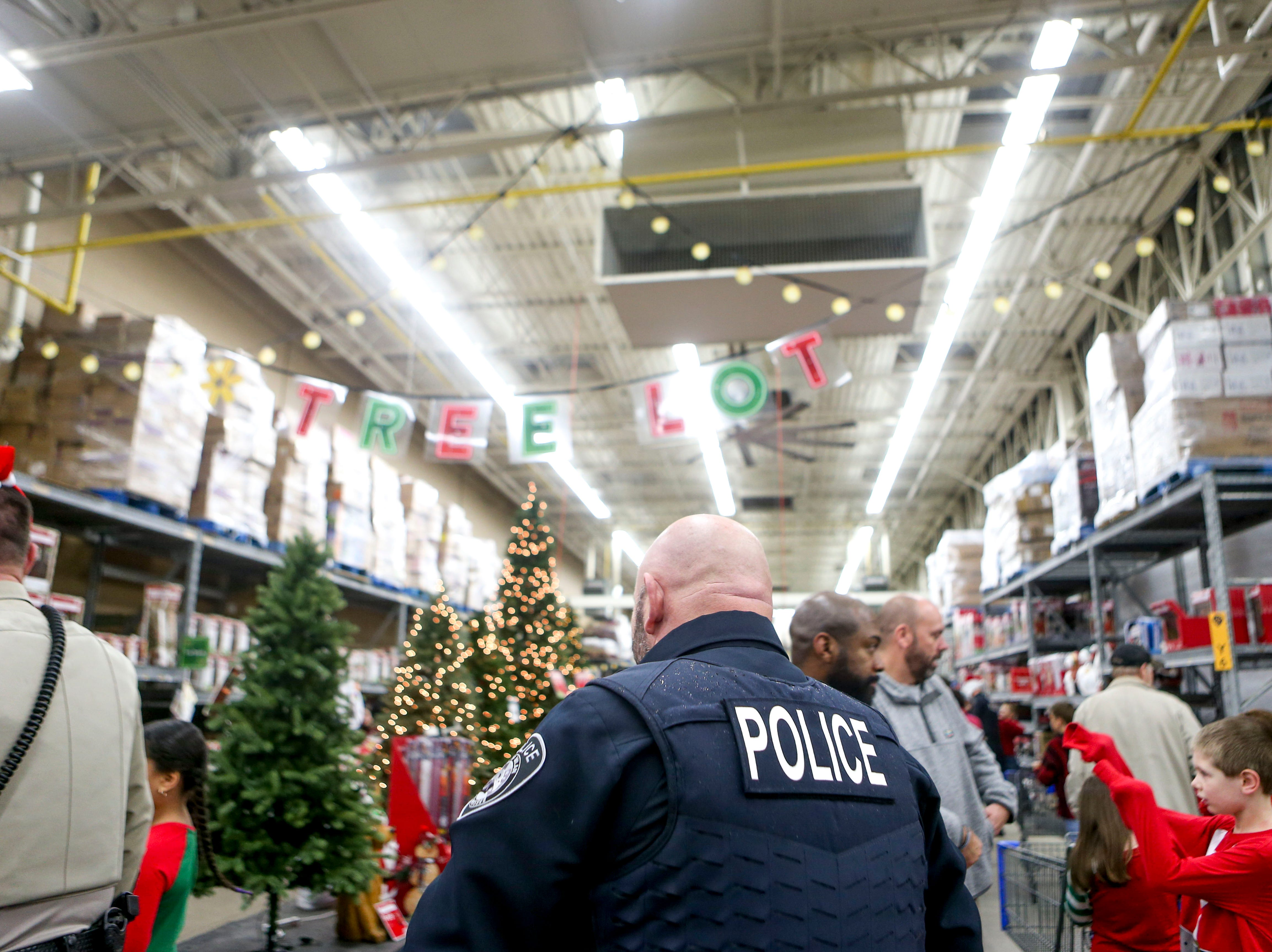 Law enforcement officers move up and down the aisles of Walmart with their partners, making it one of the safest places in Milan during shopping time for the annual Shop with a Cop program at Walmart in Milan, Tenn., on Thursday, Dec. 13, 2018.