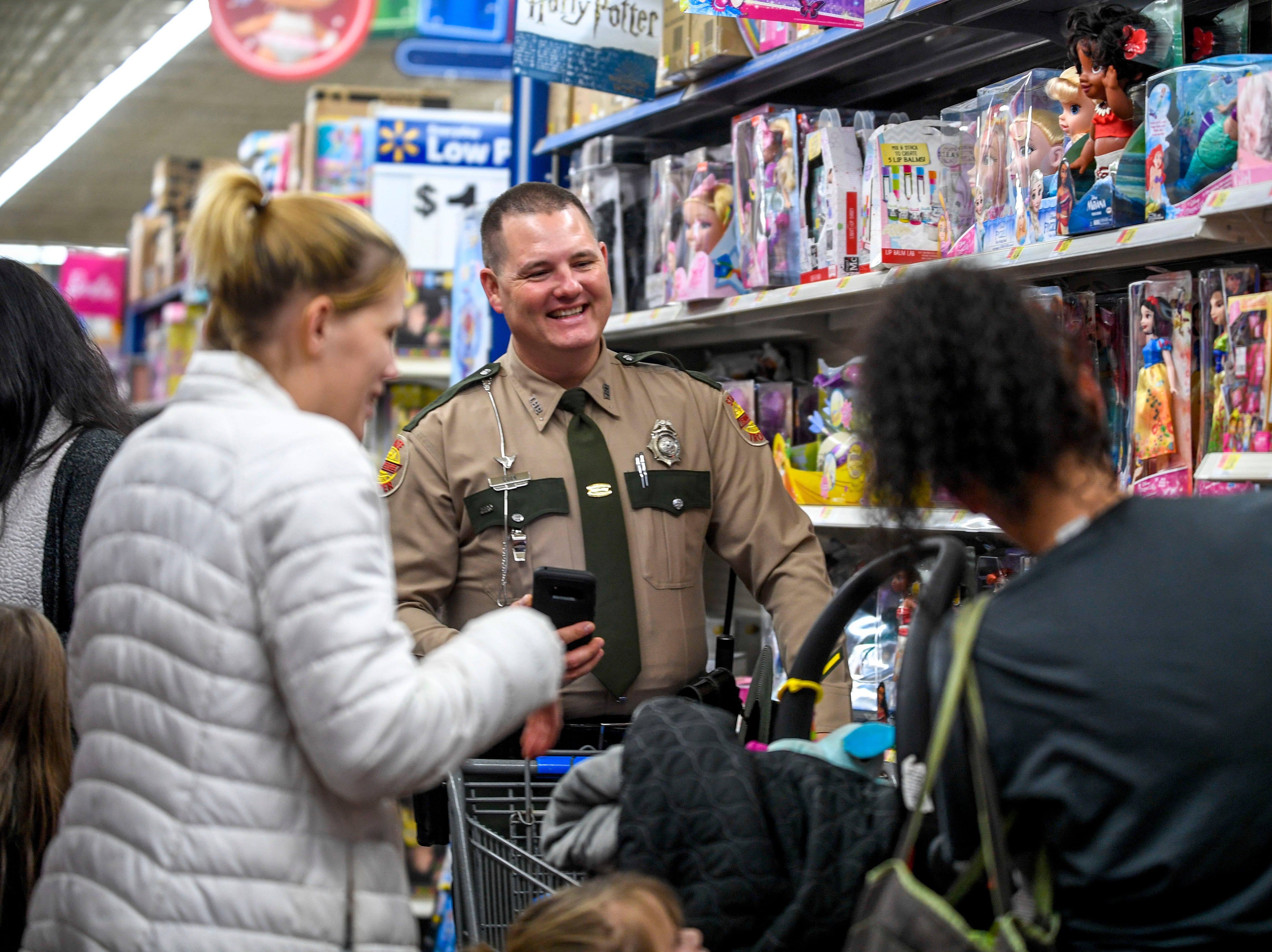 Trooper Cook helps his partners out with shopping for toys during shopping time for the annual Shop with a Cop program at Walmart in Milan, Tenn., on Thursday, Dec. 13, 2018.