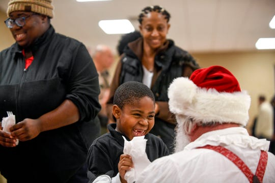 Donta Harris, 6, reacts with utter joy to seeing Santa Claus during the matching time for Shop with a Cop at Hawkins-Whitby Fema Community Safe Room in Milan, Tenn., on Thursday, Dec. 13, 2018.