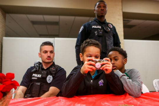 Justin Morris, a patrol officer with Trenton Police, watches as Jayden Williams, 9, left, and Jeremiah Conley, 8, right, play a video game during the matching time for Shop with a Cop at Hawkins-Whitby Fema Community Safe Room in Milan, Tenn., on Thursday, Dec. 13, 2018.