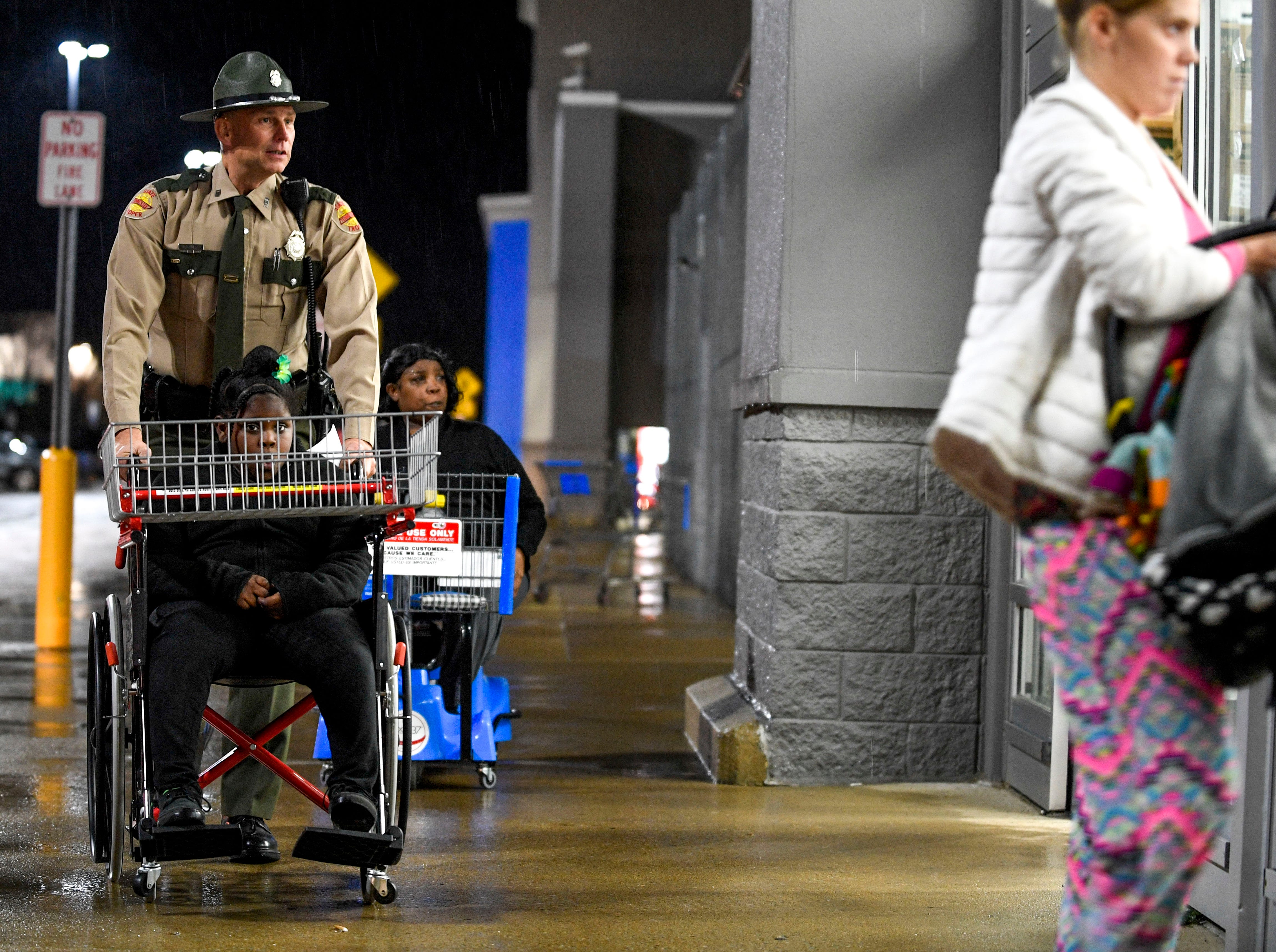 A state trooper walks into Walmart with his partner during shopping time for the annual Shop with a Cop program at Walmart in Milan, Tenn., on Thursday, Dec. 13, 2018.