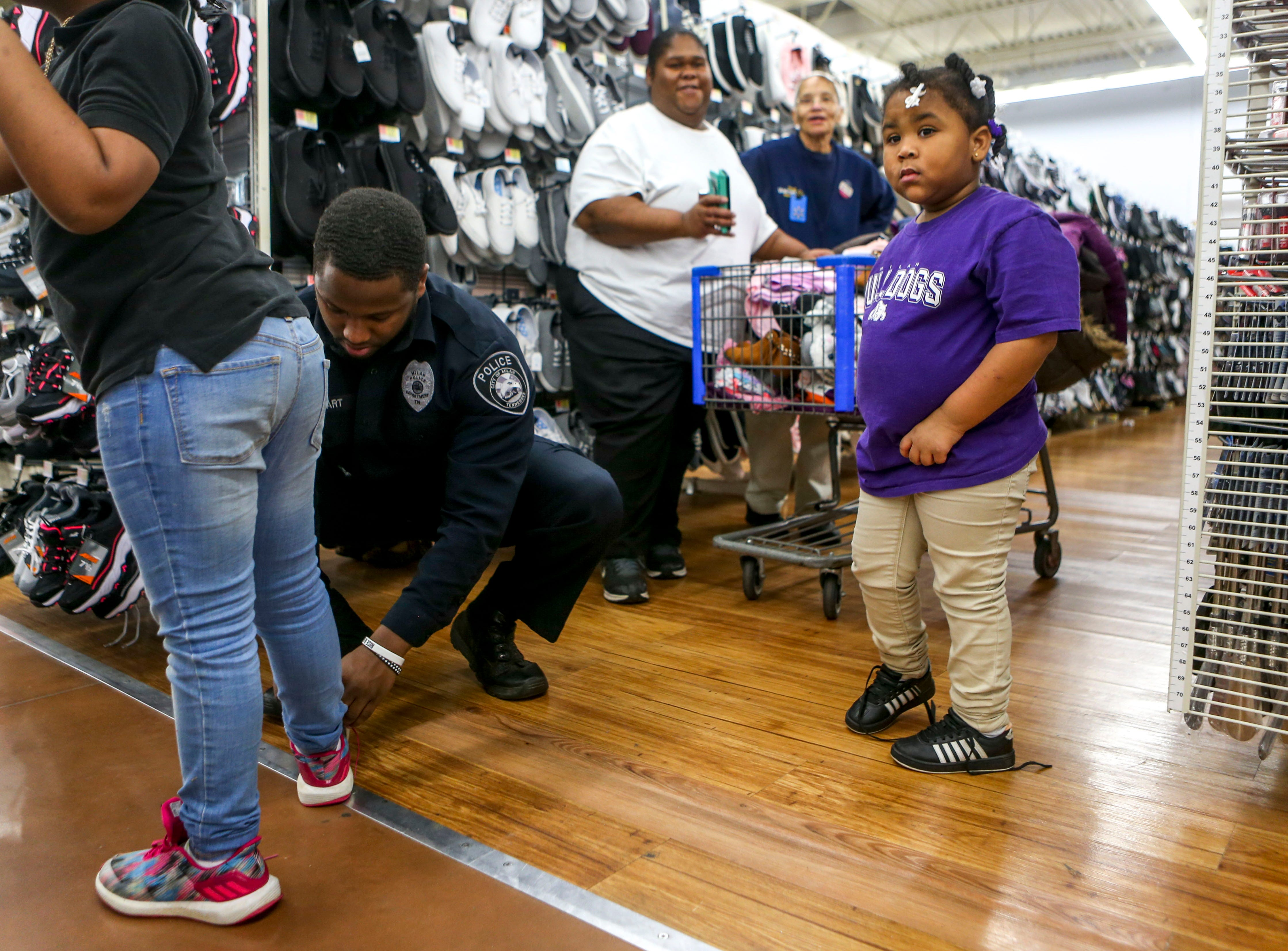Milan Police officer Hakim Hart helps tie the shoes of Beautiful Gaines, 7, while Brihanna Gaines, 4, waits for her turn to try on shoes during shopping time for the annual Shop with a Cop program at Walmart in Milan, Tenn., on Thursday, Dec. 13, 2018.
