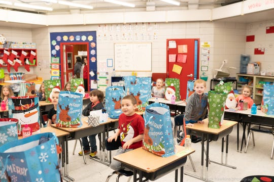 Sarah Stout's first-graders at Petros-Joyner Elementary School in Oliver Springs break into big smiles as new coats are distributed Dec. 13.