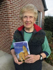 Helen Grant holds up a copy of the Second Presbyterian Church history book she recently co-wrote with her late husband, Arvilee.
