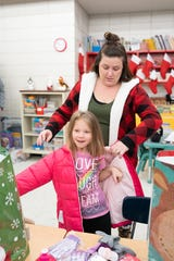 Jessica Hawkins helps Riley with her new coat.