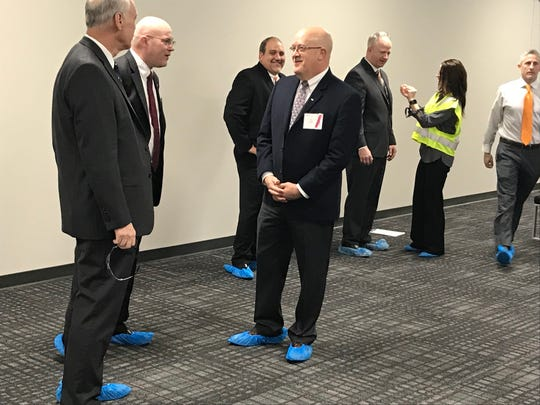 DENSO executives in shoe covers wait to greet guests at the opening of a new Maryville plant on Dec. 14, 2018.