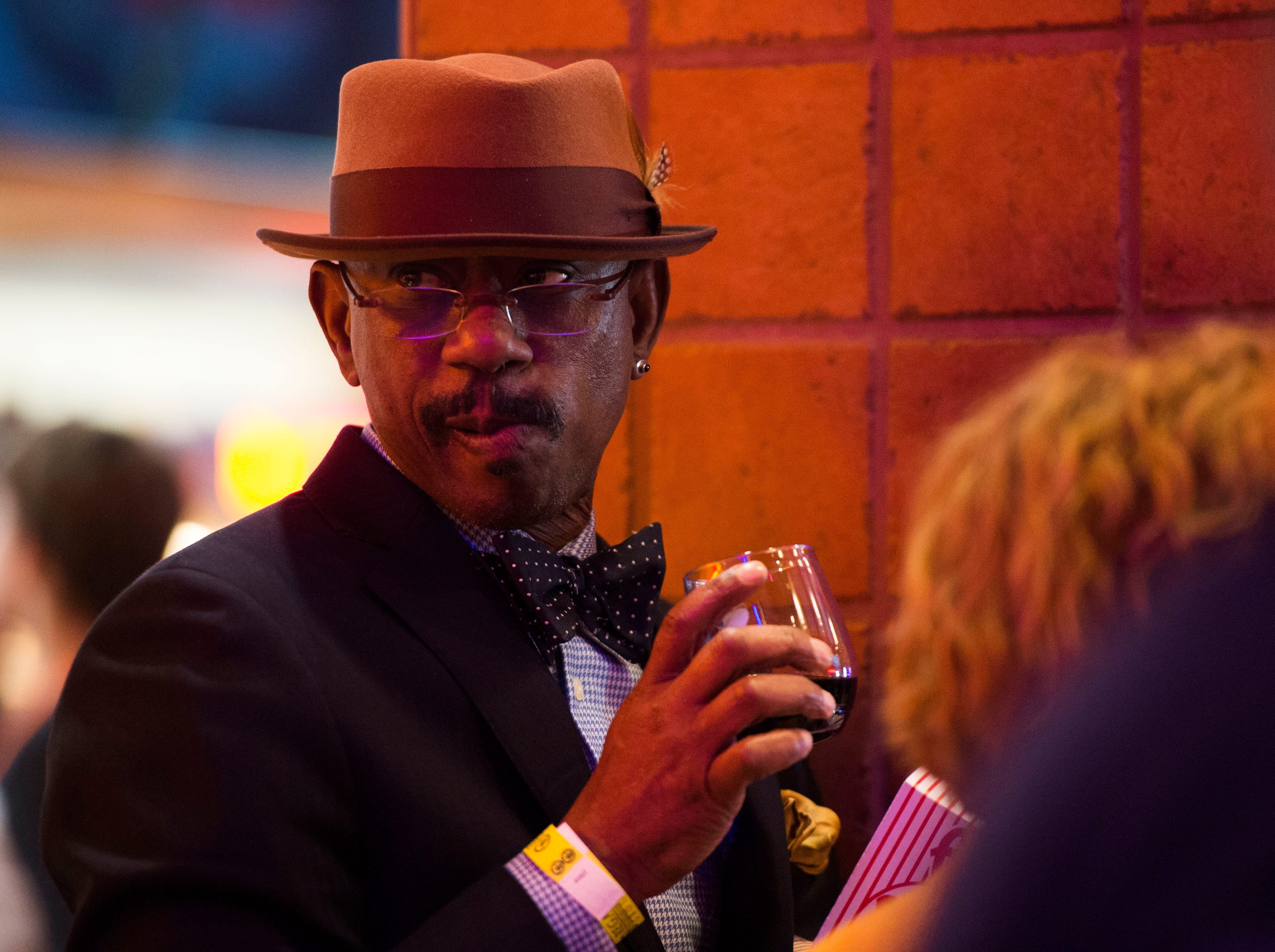 """Terry Washington of Knoxville sips a drink while waiting for """"Aquaman"""" star Patrick Wilson to arrive at Regal's annual red carpet premiere for Variety at Regal Pinnacle Stadium 18, Thursday, Dec. 13, 2018."""