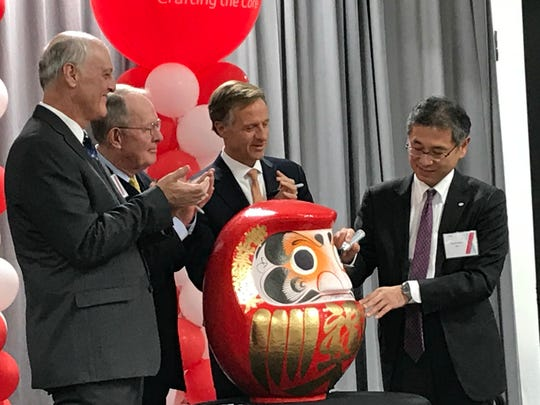 Kinichiro Ito, chairman and CEO of DENSO International America Inc. (right), colors in the left pupil of a traditional Daruma doll at the opening of DENSO's new Maryville plant Dec. 14, 2018. He colored the right pupil in October 2017 at the factory's announcement. Applauding (from left) are Jack Helmboldt, president of DENSO Manufacturing Tennessee; U.S. Sen. Lamar Alexander, R-Tennessee; and Gov. Bill Haslam.