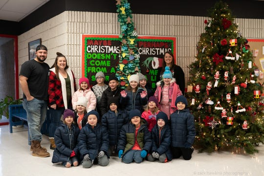 Zack Hawkins and his wife, Jessica (back left), and first-grade teacher Sarah Stout (back right) pose with students from her class at Petros-Joyner Elementary School who received coats last week.