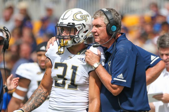 Georgia Tech Yellow Jacket Nathan Cottrell receives instructions from his coach during an ACC contest at Heinz Field against the Pitt Panthers.