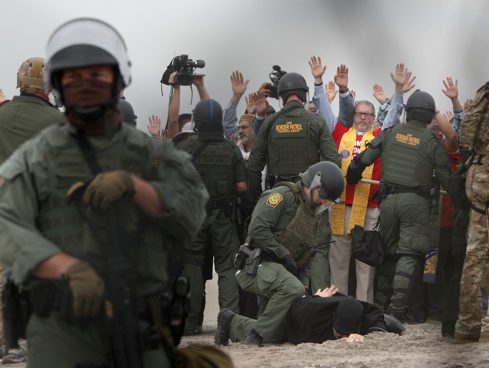 U.S. Border Patrol agents make arrests during a pro-migration protest by members of various faith groups showing support for Central American asylum-seekers who arrived in recent caravans and calling for an end to migrant detentions and deportations, in San Diego as seen through the border fence from Tijuana, Mexico, Monday, Dec. 10, 2018. Dozens of protestors were arrested for trespassing as they tried to approach the border wall, and one person for assaulting an officer. (AP Photo/Rebecca Blackwell)