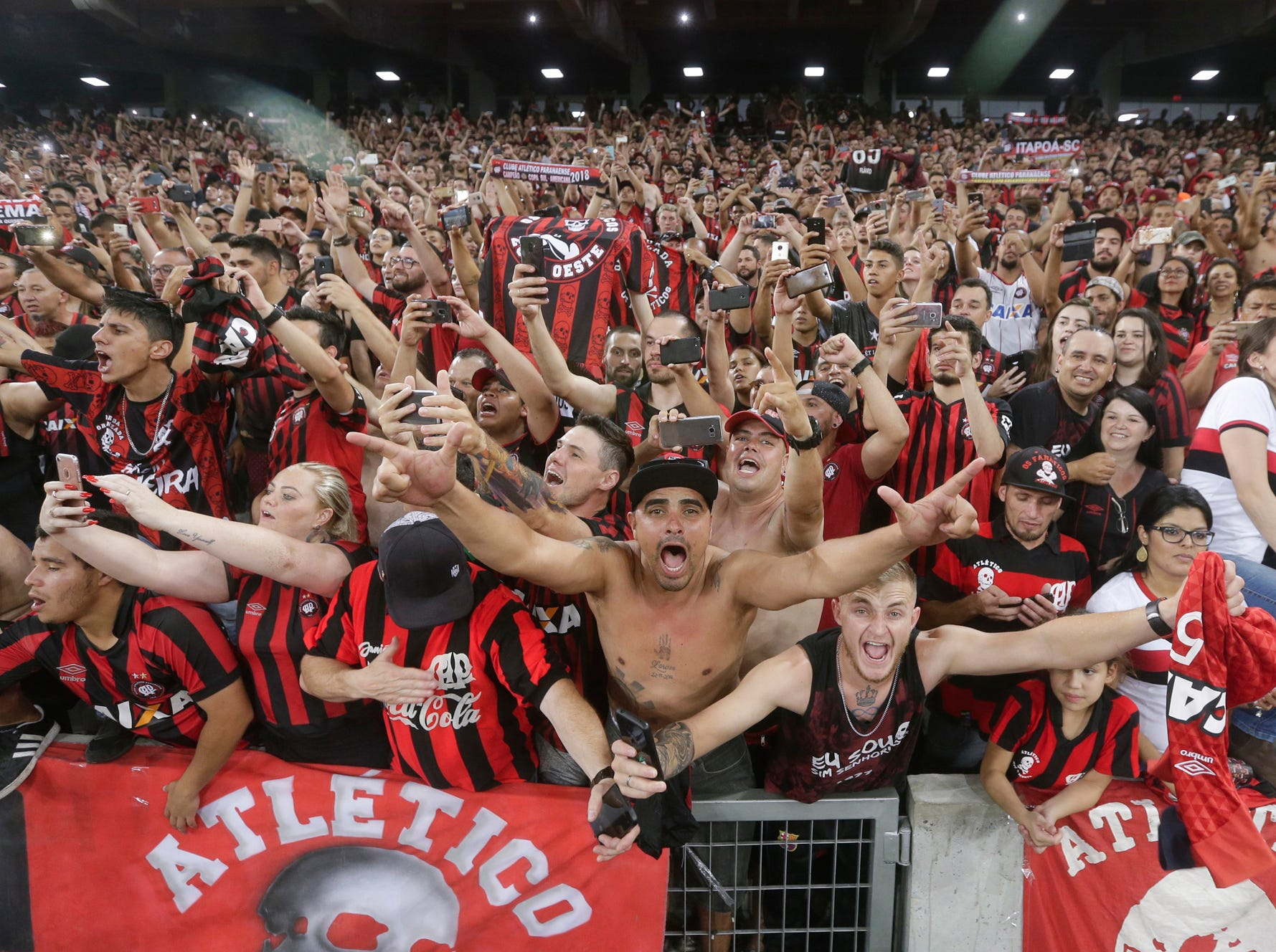Fans of Brazil's Atletico Paranaense celebrate their team's 4-3 victory over Colombia's Junior after a penalty kick shoot-out, and clenching the title of the Copa Sudamericana tournament at Arena da Baixada stadium in Curitiba, Brazil, Thursday, Dec. 13, 2018. (AP Photo/Victor Caivano)