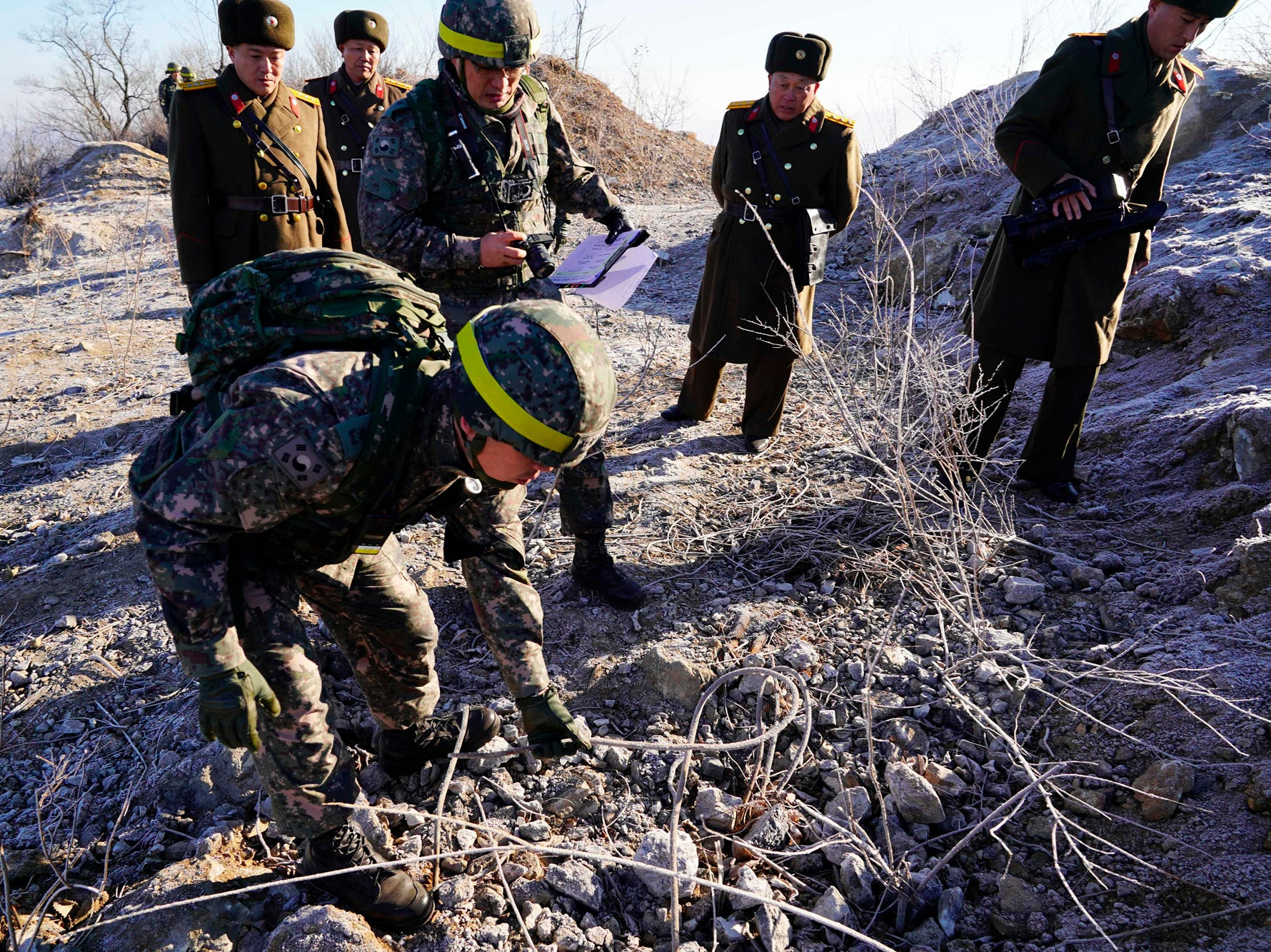 In this photo provided by South Korea Defense Ministry, South Korean army soldiers, wearing helmets, inspect at the dismantled North Korean guard post inside the Demilitarized Zone (DMZ) in the central section of the inter-Korean border in Cheorwon, Wednesday, Dec. 12, 2018. Dozens of North and South Korean soldiers crossed over the world's most heavily armed border Wednesday as they inspected the sites of their rival's front-line guard posts to verify they'd been removed, part of inter-Korean engagement efforts that come amid stalled U.S.-North Korea nuclear disarmament talks. (South Korea Defense Ministry via AP)