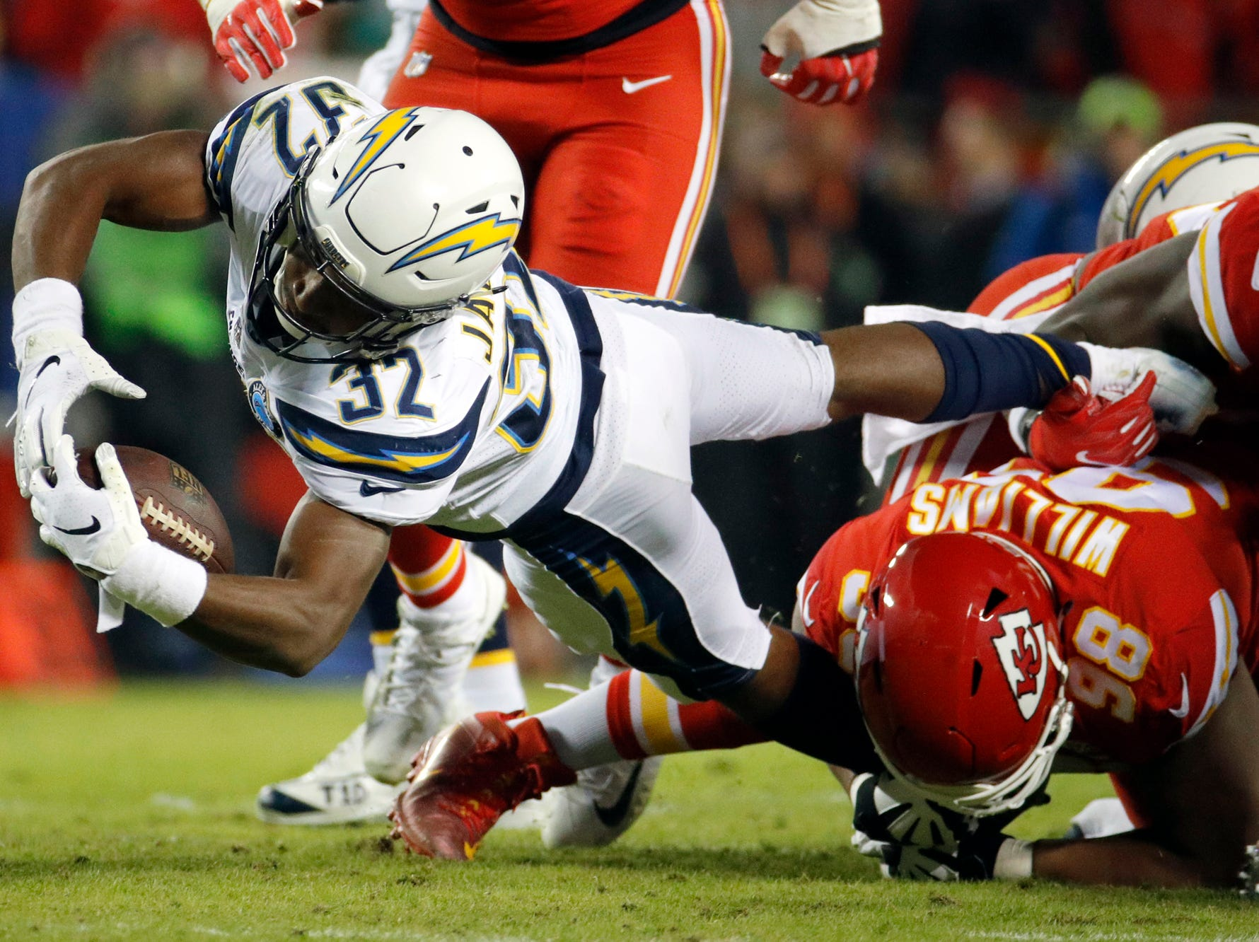 Los Angeles Chargers running back Justin Jackson (32) is tackled by Kansas City Chiefs tackle Xavier Williams (98) during the first half of an NFL football game in Kansas City, Mo., Thursday, Dec. 13, 2018. (AP Photo/Charlie Riedel)