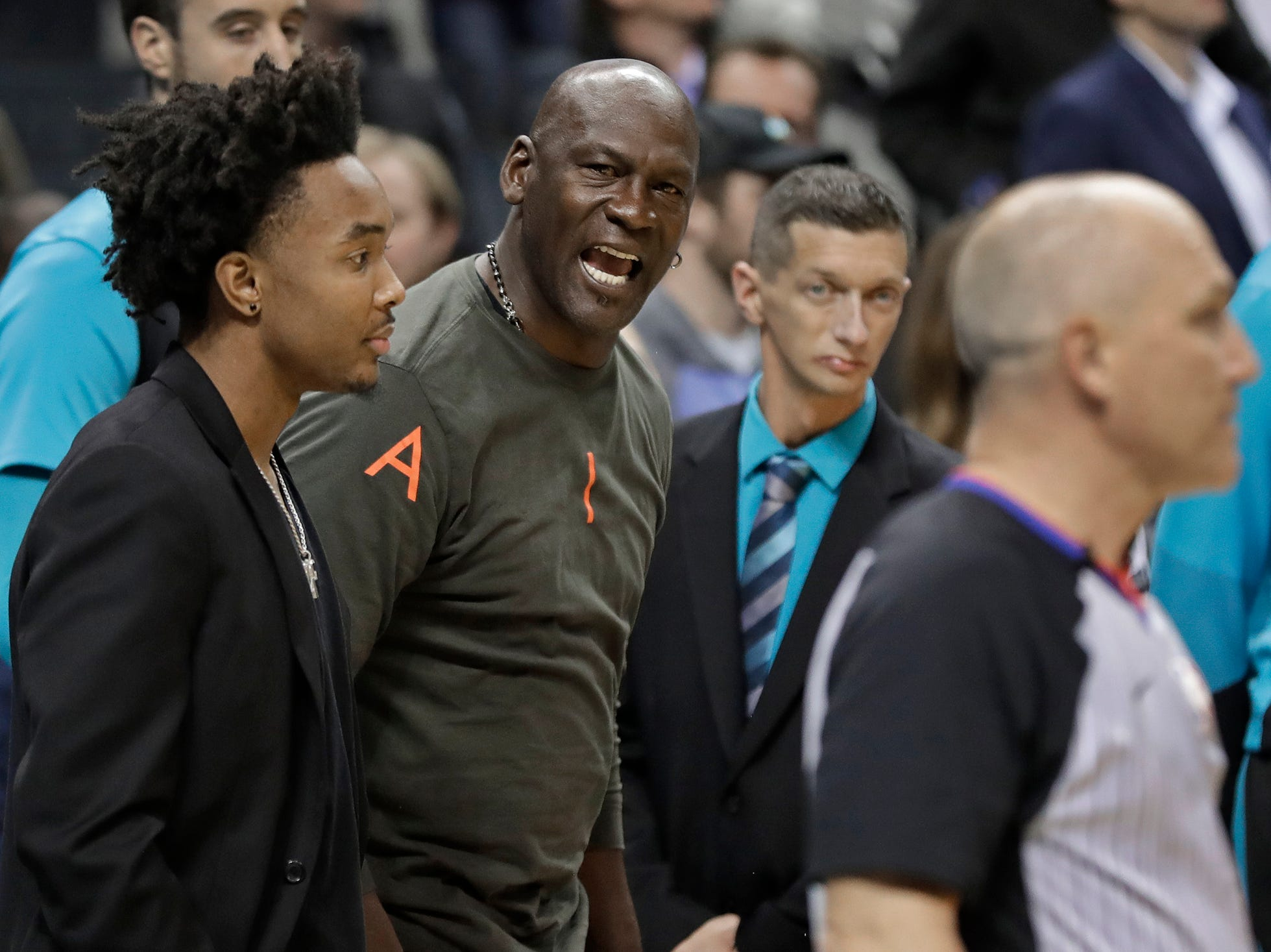 Charlotte Hornets owner Michael Jordan, center, shouts at an official in the final seconds of the second half of an NBA basketball game against the Detroit Pistons in Charlotte, N.C., Wednesday, Dec. 12, 2018. Officials ruled the Hornets had six players on the floor in the final second of the game, giving one free throw to Detroit. The Hornets won 108-107. (AP Photo/Chuck Burton)