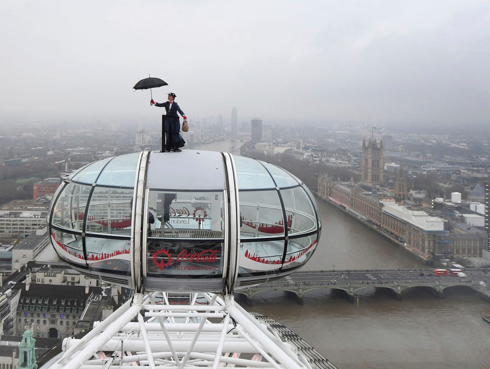 Ahead of the European movie premiere of Mary Poppins Returns, a Mary Poppins stunt double rides atop of the London Eye in central London with the Houses of Parliament on the banks of the River Thames, right, Wednesday Dec. 12, 2018. (Joe Giddens/PA via AP)