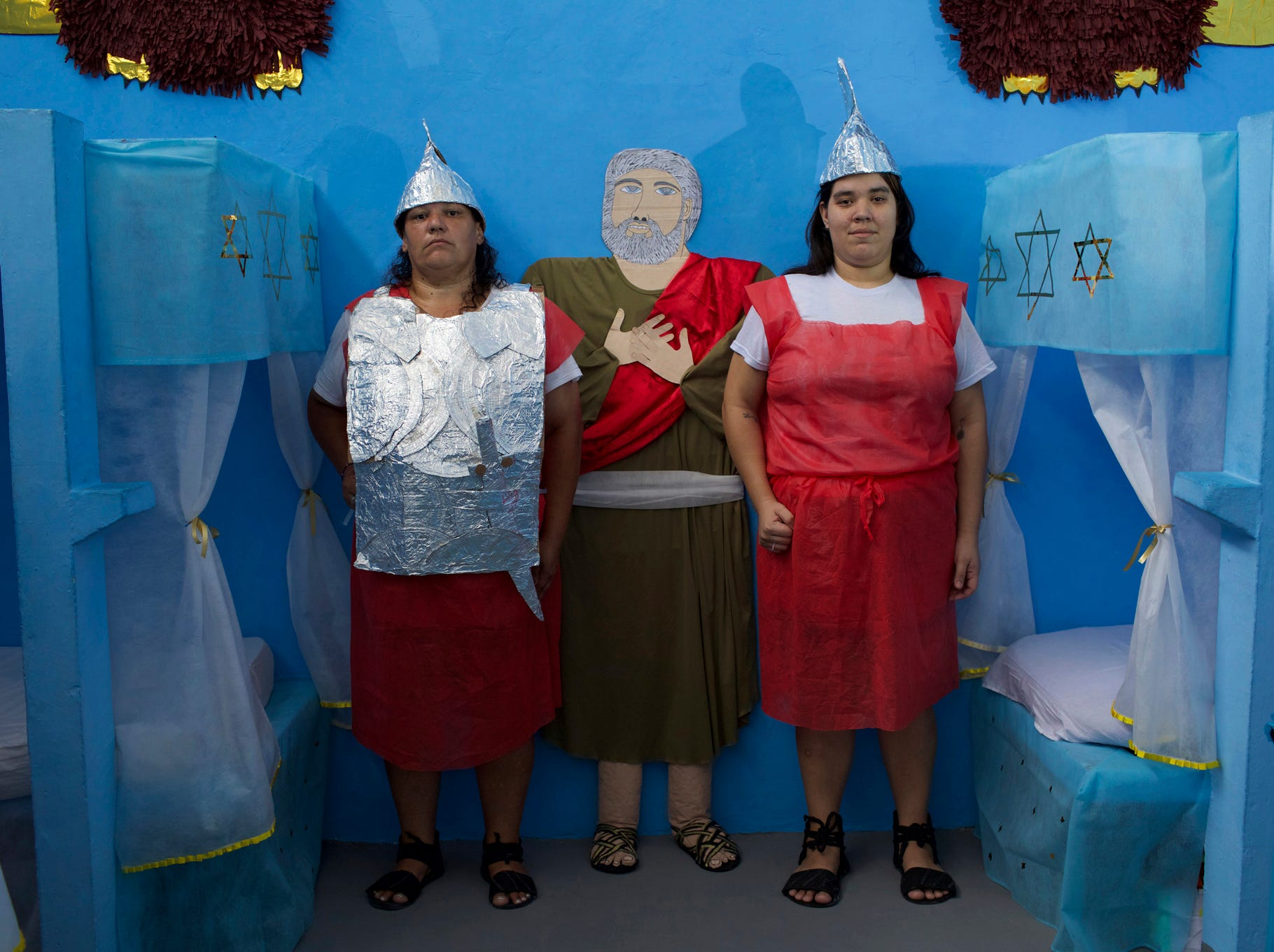 Female inmates dressed as guards pose for a photo during Nelson Hungria Prison's annual Christmas event for inmates and jail staff in Rio de Janeiro, Brazil, Thursday, Dec. 13, 2018. Inmates serving time for offenses from burglary to homicide spent weeks decking out their cell blocks with handmade Christmas decorations and planning Bible related performances. (AP Photo/Silvia Izquierdo)