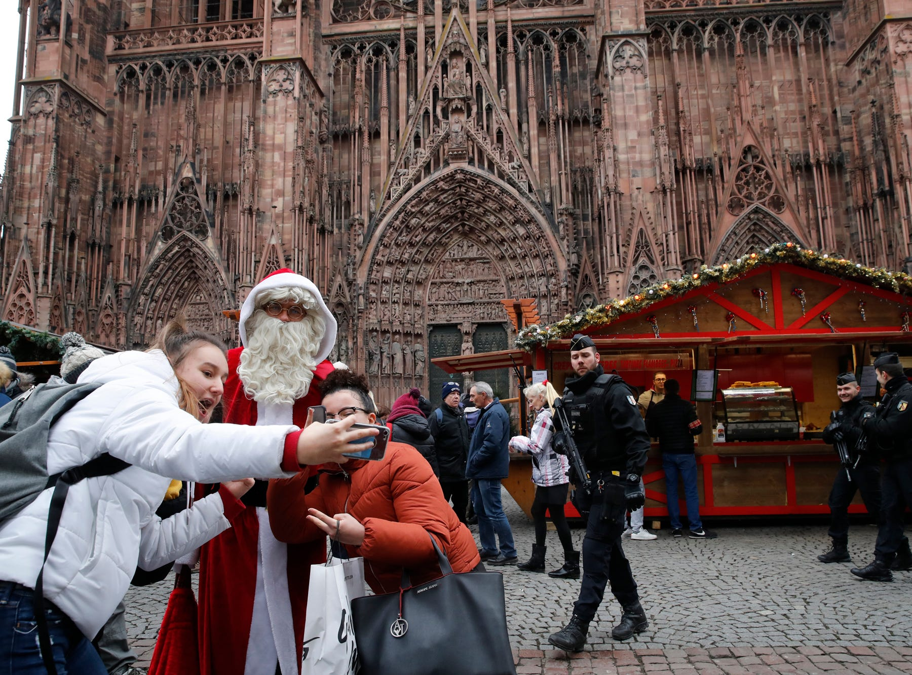 People take a selfie with man dressed like a Santa Claus as police officers patrol outside the cathedral in Strasbourg, eastern France, Friday, Dec.14, 2018. The man authorities believe killed three people during a rampage near a Christmas market in Strasbourg died Thursday in a shootout with police at the end of a two-day manhunt, French authorities said. (AP Photo/Christophe Ena)
