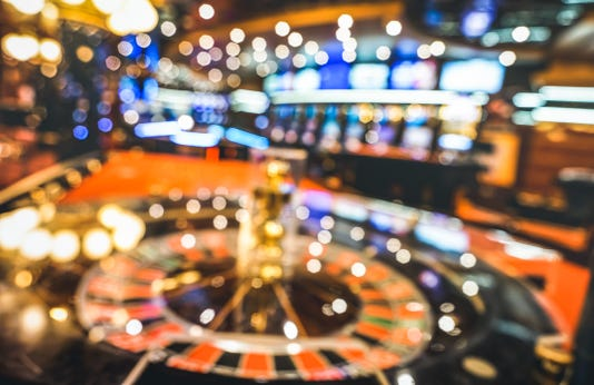 Blurred Defocused Background Of Roulette At Casino Saloon Gambling Concept With Unfocused Game Room With Video Poker Slot Machines And Multicolored Blurry Lights