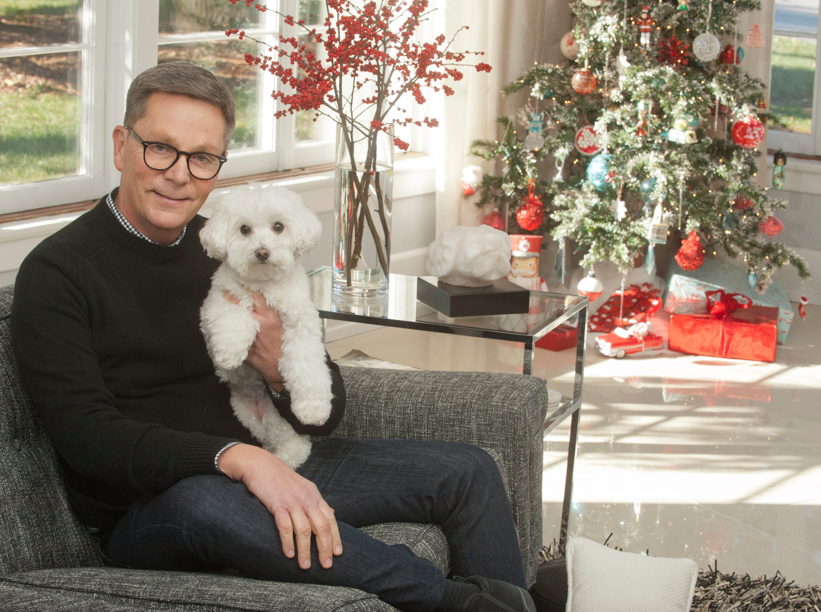 Lindy Casebier holds his dog, Mamie relax in the family living room.10 December 2018
