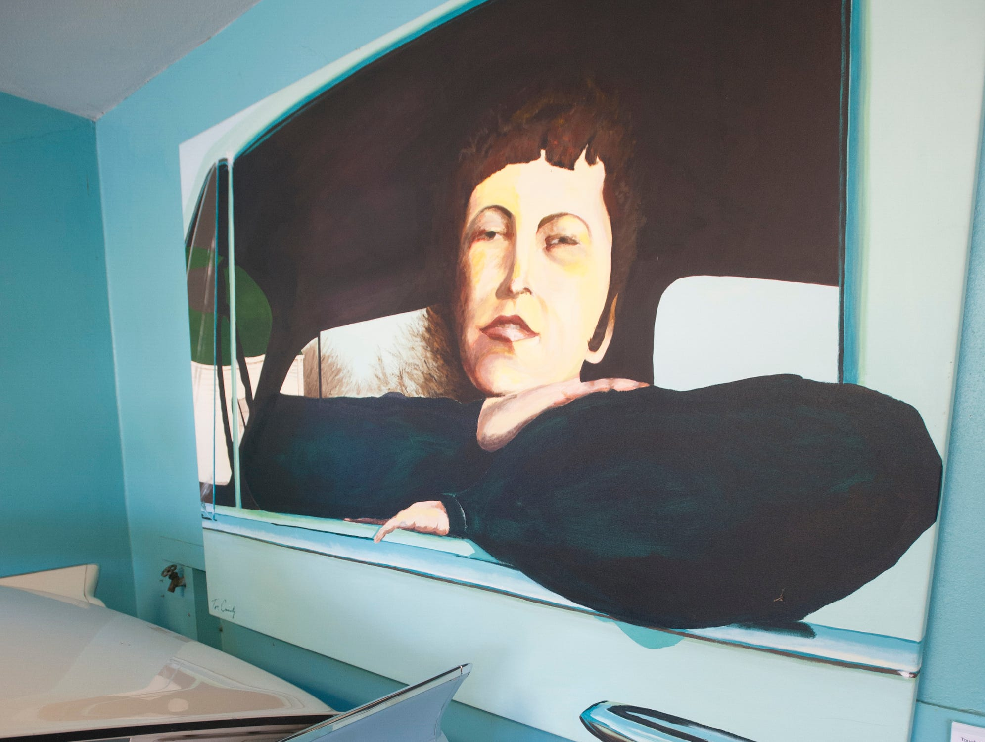 """The Cannady painting """"Touch Football, Anyone?,"""" hangs at the rear of a Ford Skyline in the home's garage. The room is filled with Cannady's auto-themed artwork, and pieces are occasionally exchanged with those inside to keep the decor fresh.10 December 2018"""