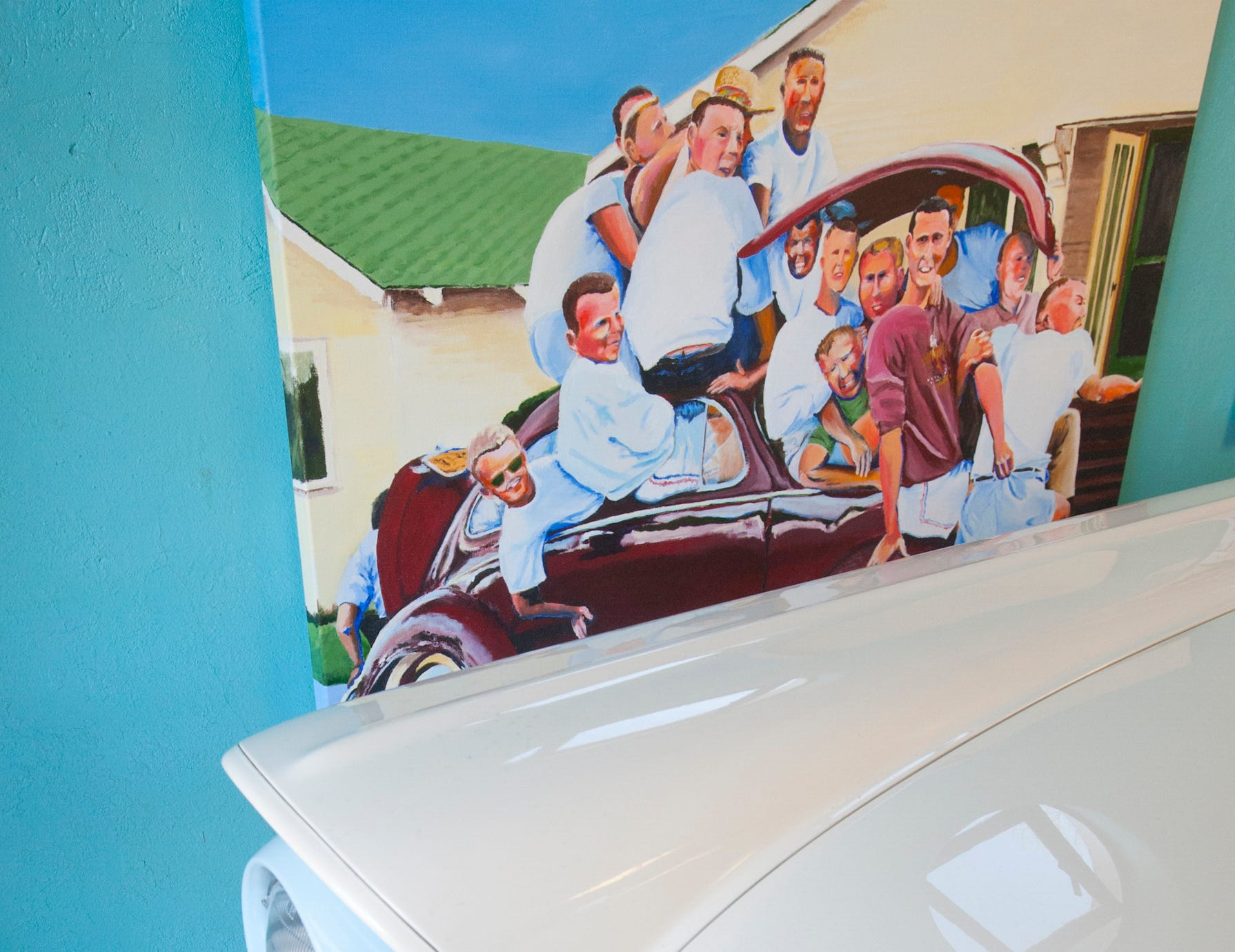 """The Cannady painting """"Scootch Over, Hun,"""" pops out from the front of a Ford Skyline in the home's garage. The room is filled with Cannady's auto-themed artwork, and pieces are occasionally exchanged with those inside to keep the decor fresh.10 December 2018"""