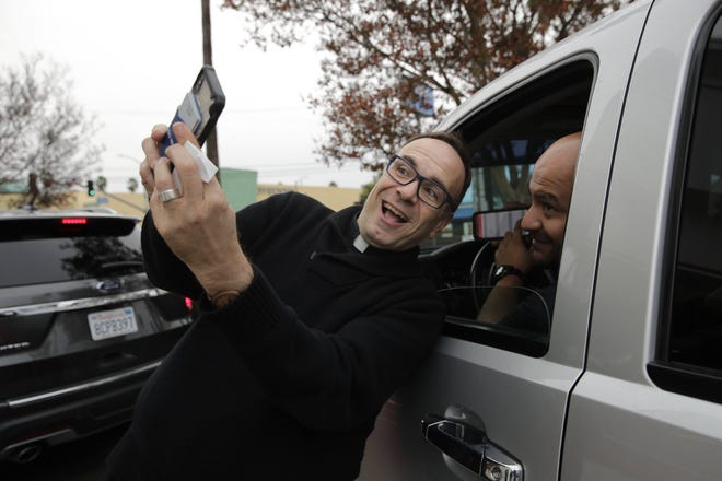 Father Jim Sichko takes a selfie with a drive-thru customer after paying for the man's meal at a California In-N-Out Burger. Dec. 5, 2018